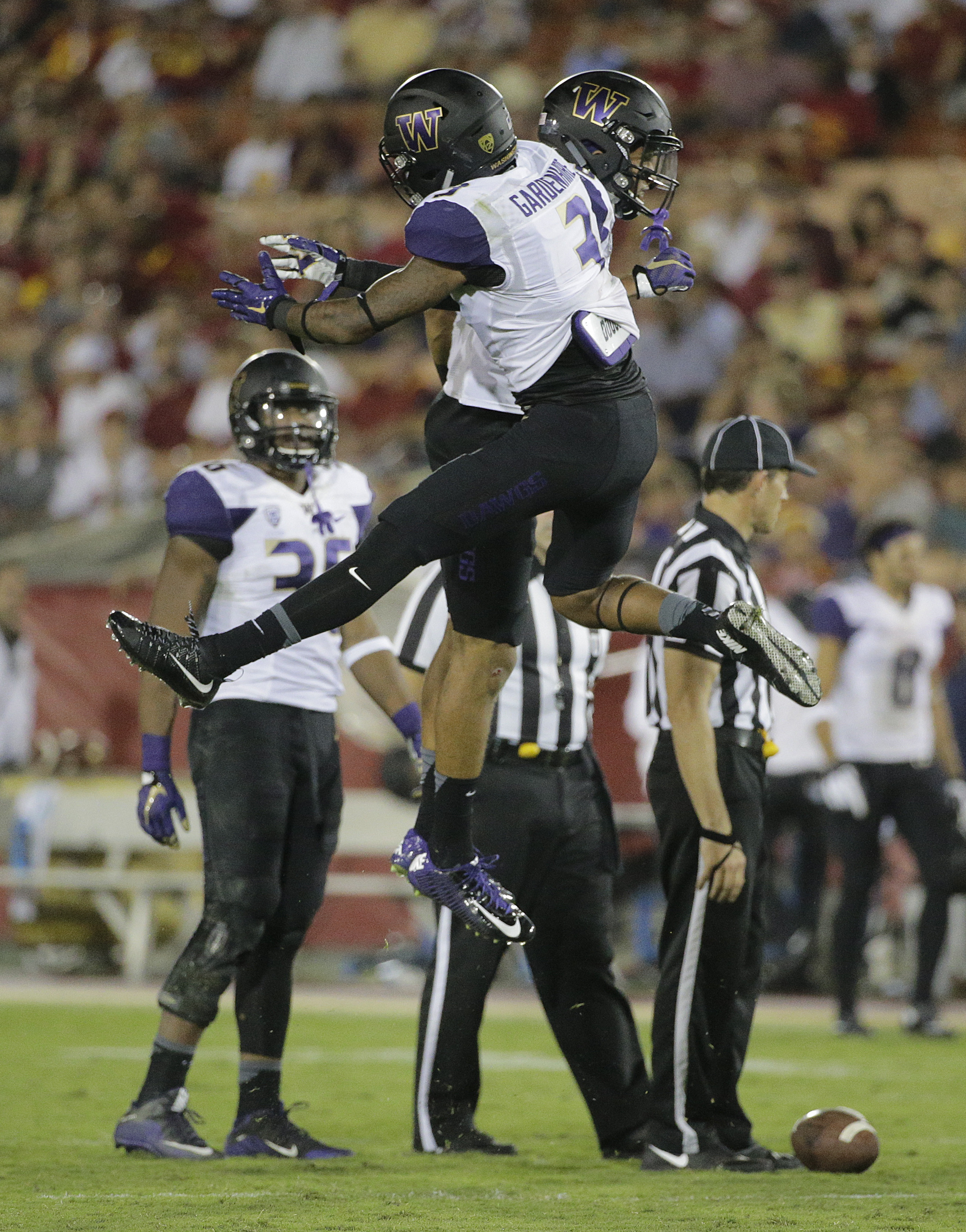 Washington's Darren Gardenhire, front, and Sidney Jones celebrate after their teammate recovered a fumble during the second half of an NCAA college football game against Southern California , Thursday, Oct. 8, 2015, in Los Angeles. Washington won 17-12. (