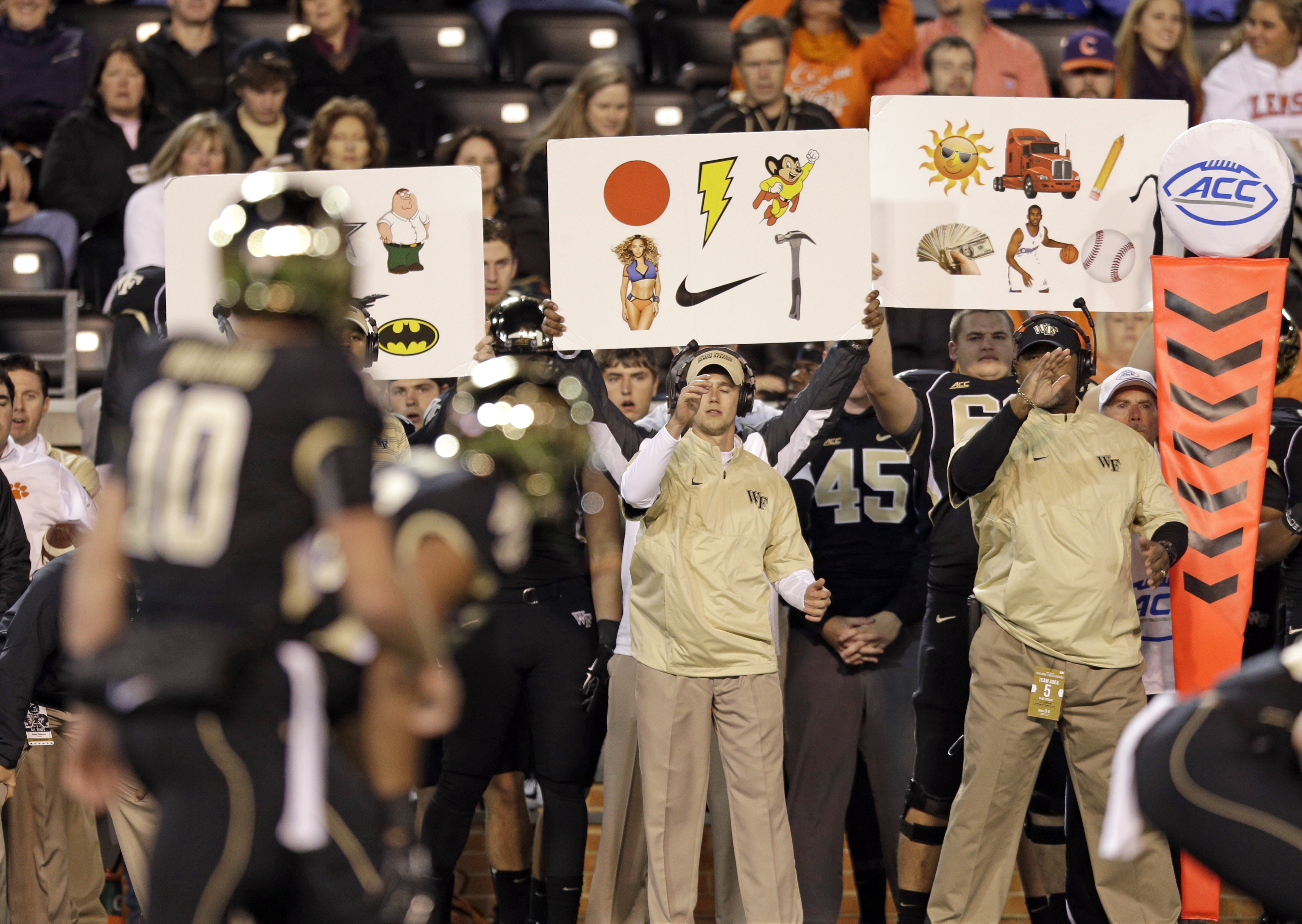 FILE - In this Nov. 6, 2014, file photo, Wake Forest coaches use signs to signal in a play during the first half of an NCAA college football game against Clemson in Winston-Salem, N.C. Once a technique used to replace hand signals for offenses, in the pas