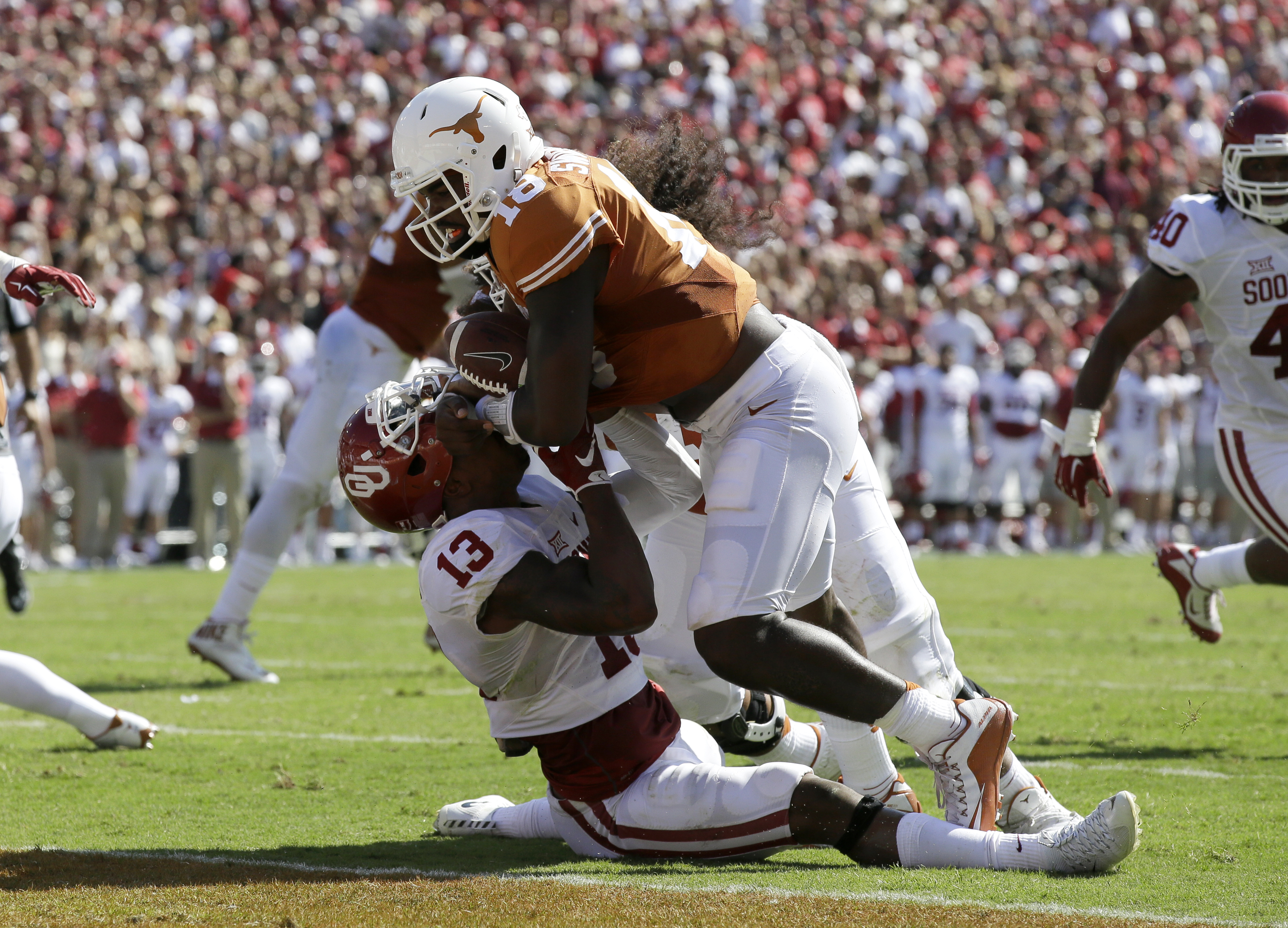 Texas quarterback Tyrone Swoopes struggles to hold onto the ball as he crosses the goal line for a touchdown over Oklahoma safety Ahmad Thomas in the first half of an NCAA college football game Saturday, Oct. 10, 2015, in Dallas. Swoopes was credited with