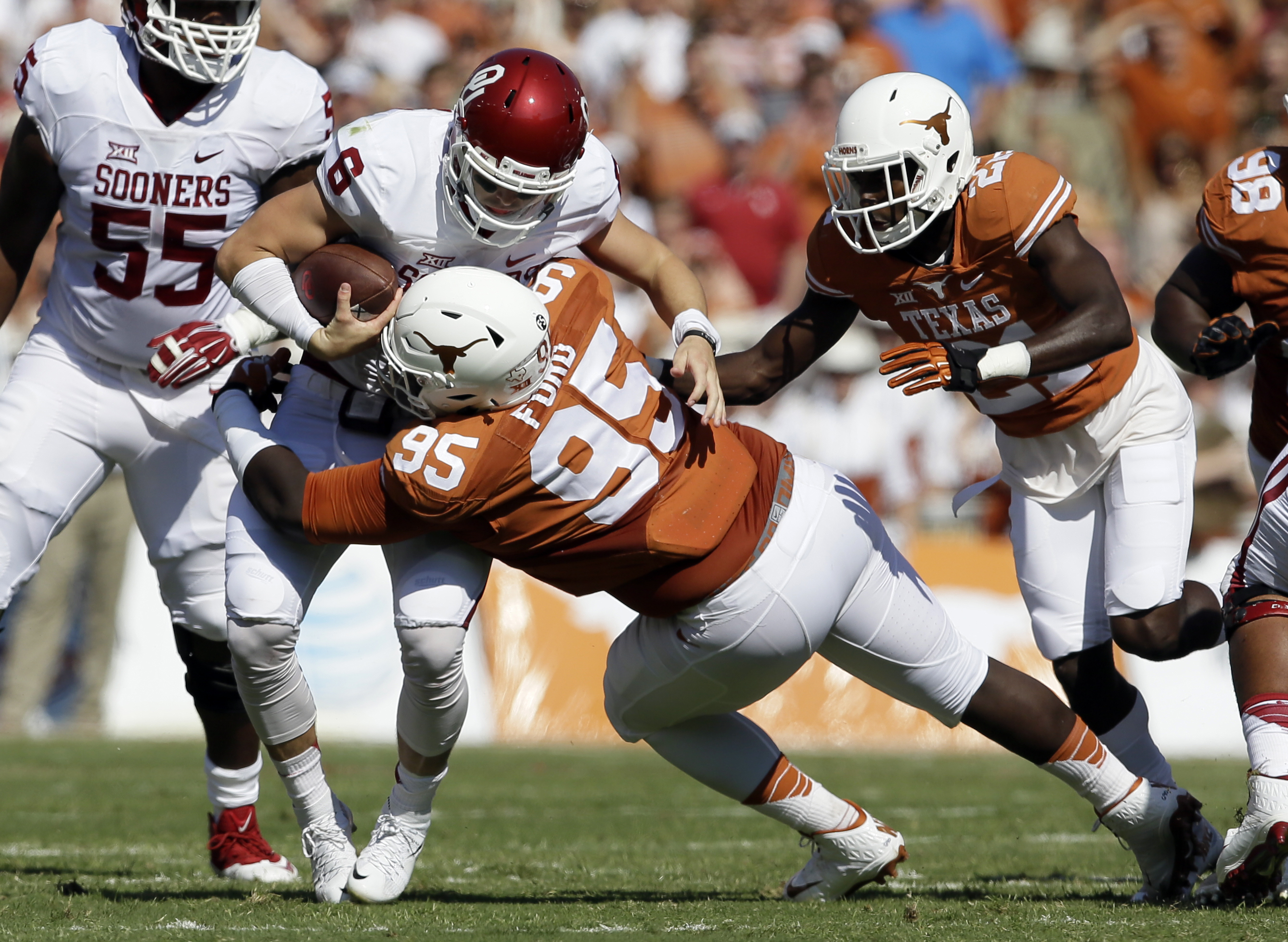 Texas defensive tackle Poona Ford (95) sacks Oklahoma quarterback Baker Mayfield (6) in the first half of an NCAA college football game Saturday, Oct. 10, 2015, in Dallas. (AP Photo/LM Otero)