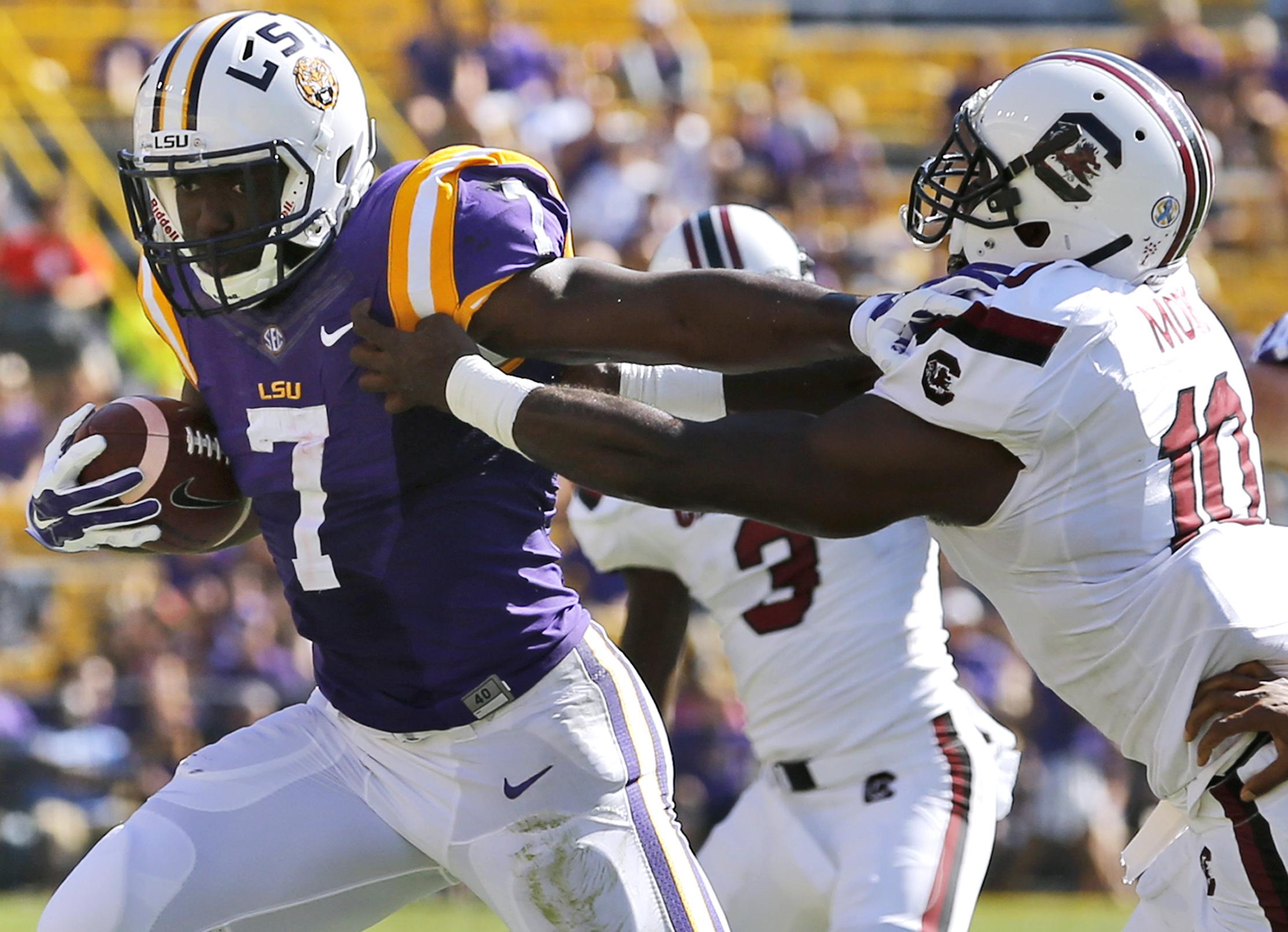 LSU running back Leonard Fournette (7) stiff arms South Carolina linebacker Skai Moore (10) during the first half of an NCAA college football game in Baton Rouge, La., Saturday, Oct. 10, 2015. (AP Photo/Jonathan Bachman)