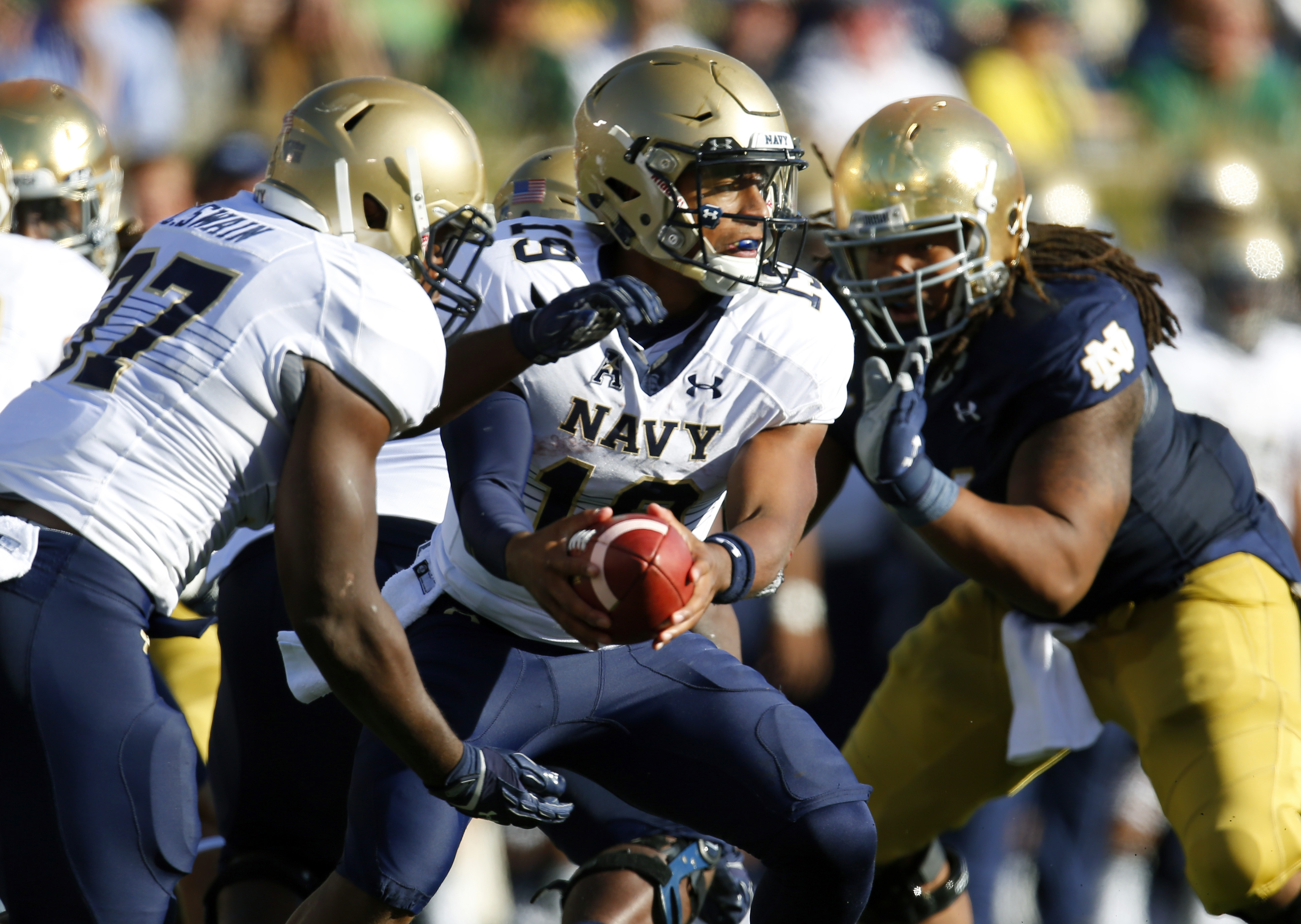 Navy quarterback Keenan Reynolds (19) looks to hand off to fullback Chris Swain during the first half of an NCAA college football game against Notre Dame, Saturday, Oct. 10, 2015, in South Bend, Ind. (AP Photo/Jeff Haynes)