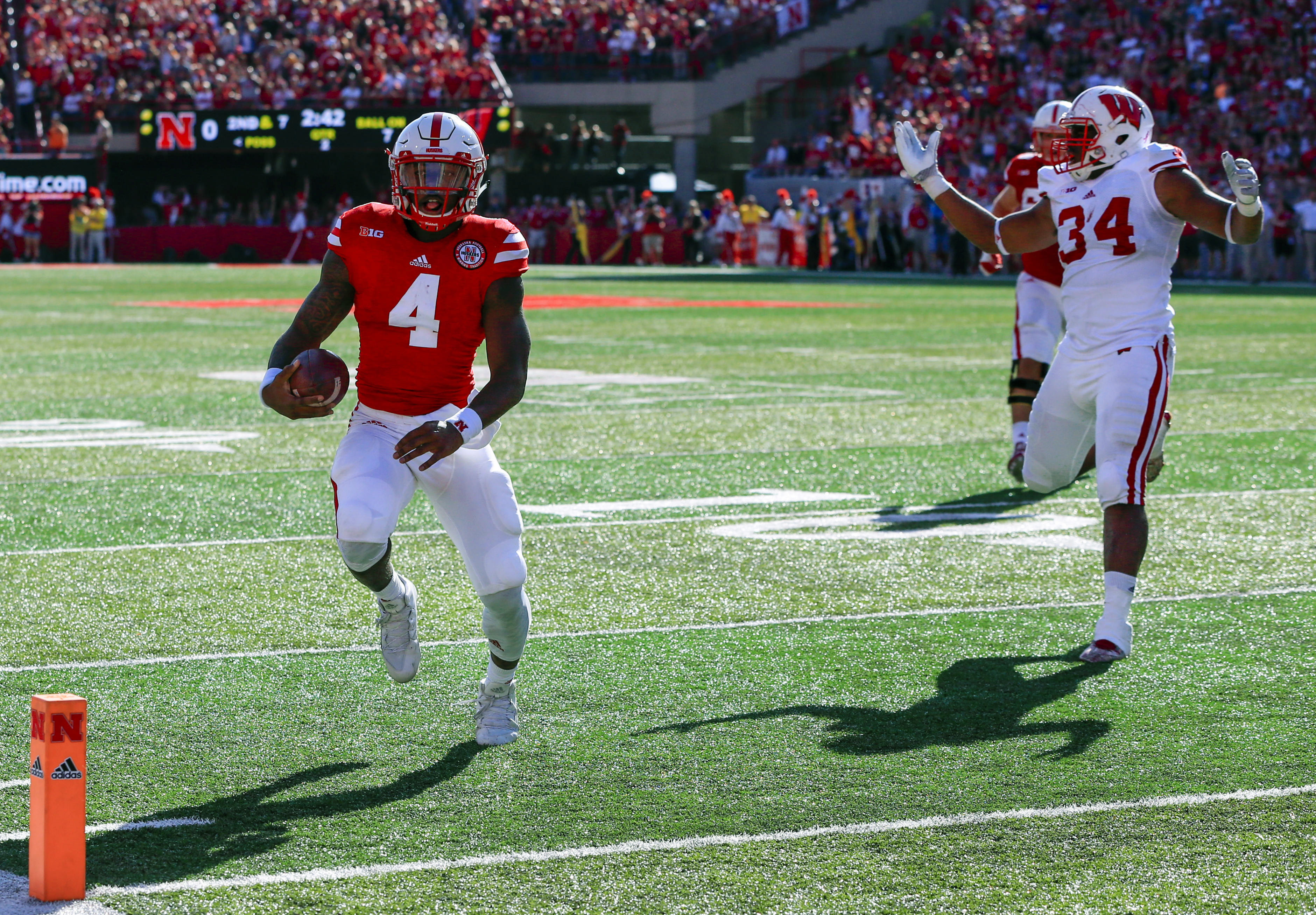 Nebraska quarterback Tommy Armstrong Jr. (4) runs for a touchdown ahead of Wisconsin defensive end Chikwe Obasih (34) during the first half of an NCAA college football game in Lincoln, Neb., Saturday, Oct. 10, 2015. (AP Photo/Nati Harnik)