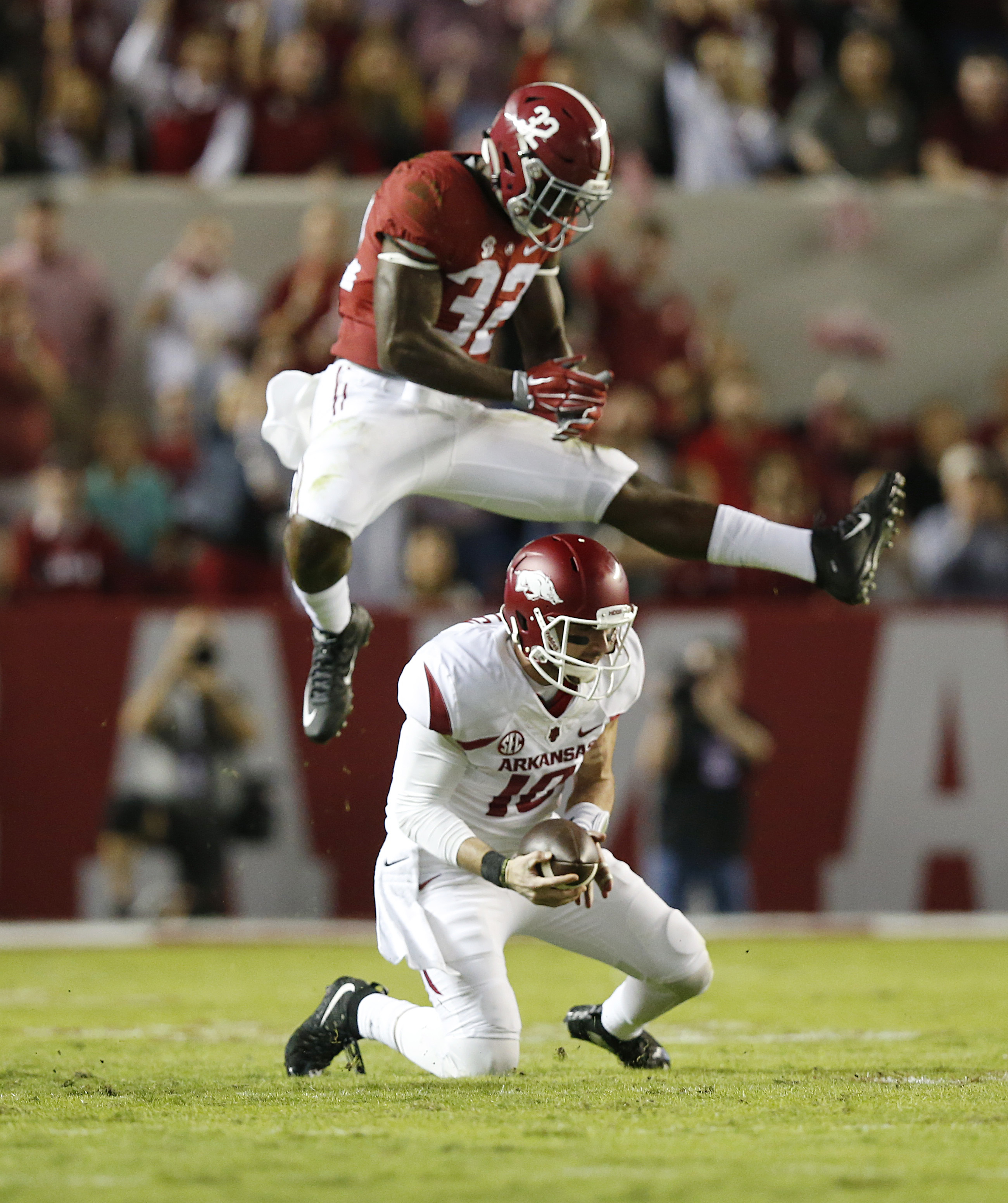 Alabama linebacker Rashaan Evans (32) jumps over Arkansas quarterback Brandon Allen (10) in the first half of an NCAA college football game, Saturday, Oct. 10, 2015, in Tuscaloosa, Ala. (AP Photo/Brynn Anderson)