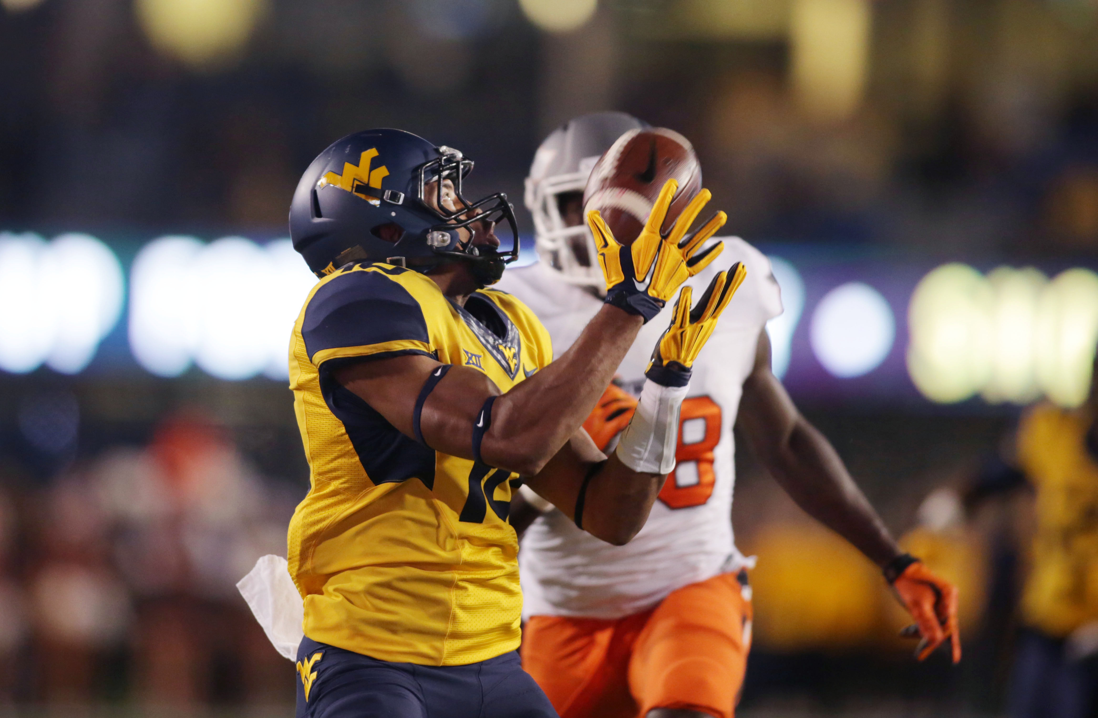 West Virginia cornerback Terrell Chestnut (16) intercepts the football after beating Oklahoma State wide receiver James Washington (28) to the pass during the first half of an NCAA college football game, Saturday, Oct. 10, 2015, in Morgantown, W.Va. (AP P