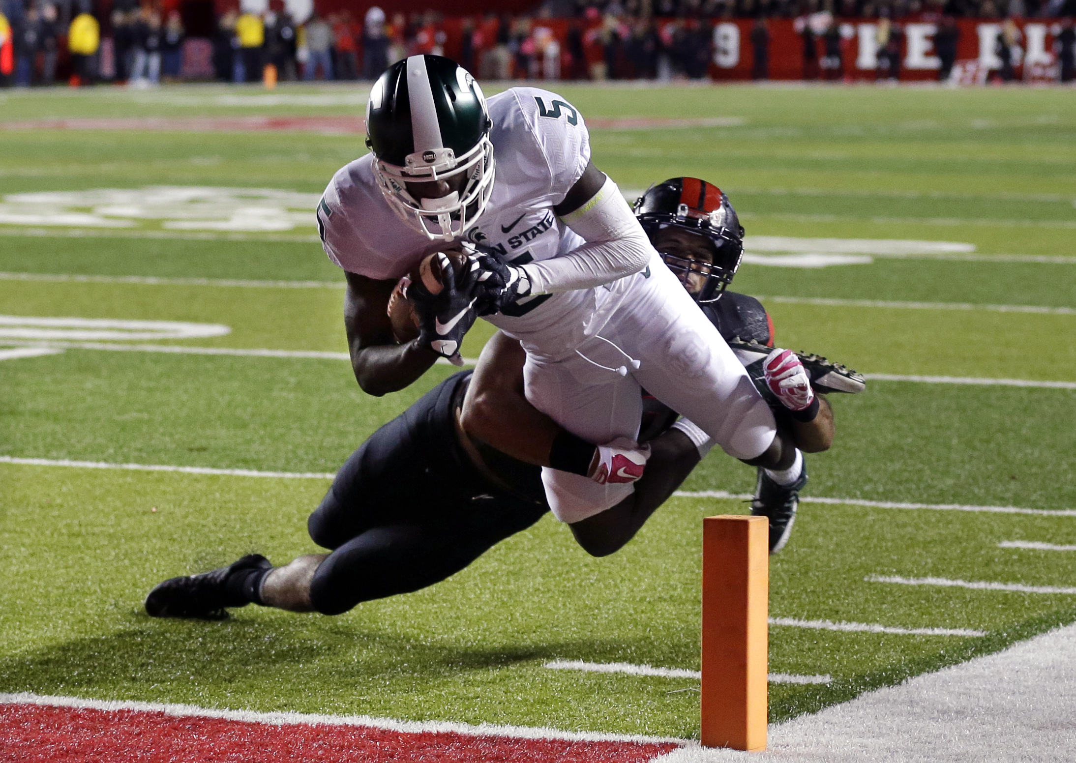Michigan State wide receiver DeAnthony Arnett (5) dives for a touchdown as Rutgers defensive back Andre Hunt (30) cannot make a tackle during the second half of an NCAA college football game Saturday, Oct. 10, 2015, in Piscataway, N.J. (AP Photo/Mel Evans