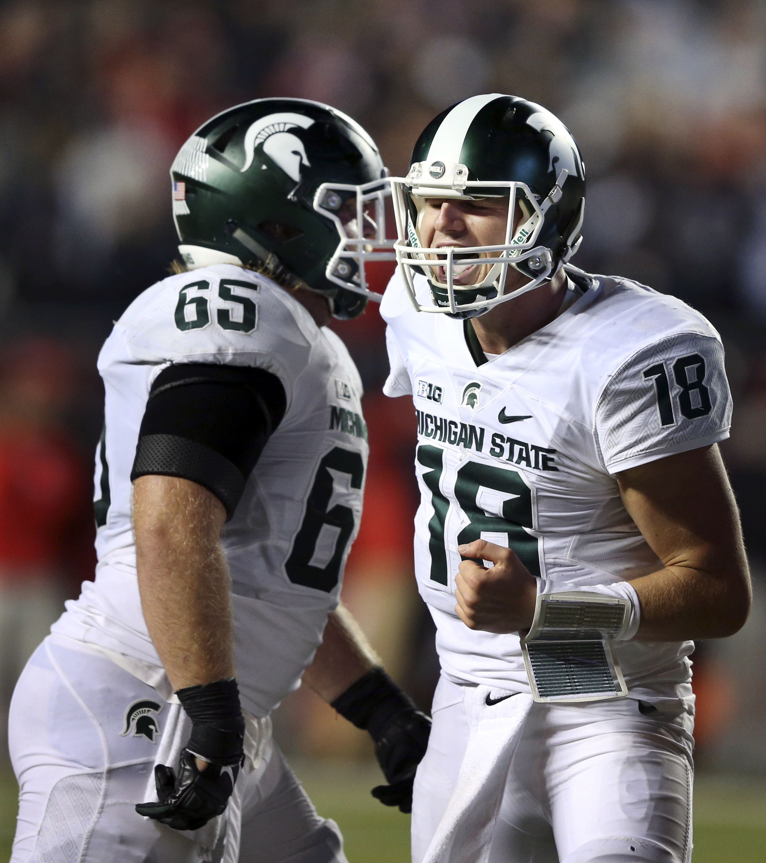 Michigan State quarterback Connor Cook (18) celebrates with offensive lineman Brian Allen (65) late in the second half of an NCAA college football game against Rutgers Saturday, Oct. 10, 2015, in Piscataway, N.J. Michigan State won 31-24. (AP Photo/Mel Ev