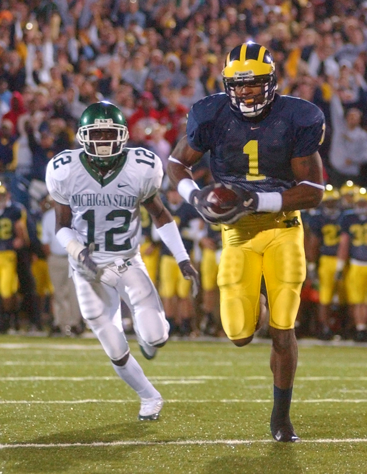 FILE - In this Oct. 20, 2004, file photo, Michigan wide receiver Braylon Edwards (1) outruns Michigan State cornerback Aston Watson (12) for a touchdown during the third overtime period of an NCAA college football game at Michigan Stadium in Ann Arbor, Mi