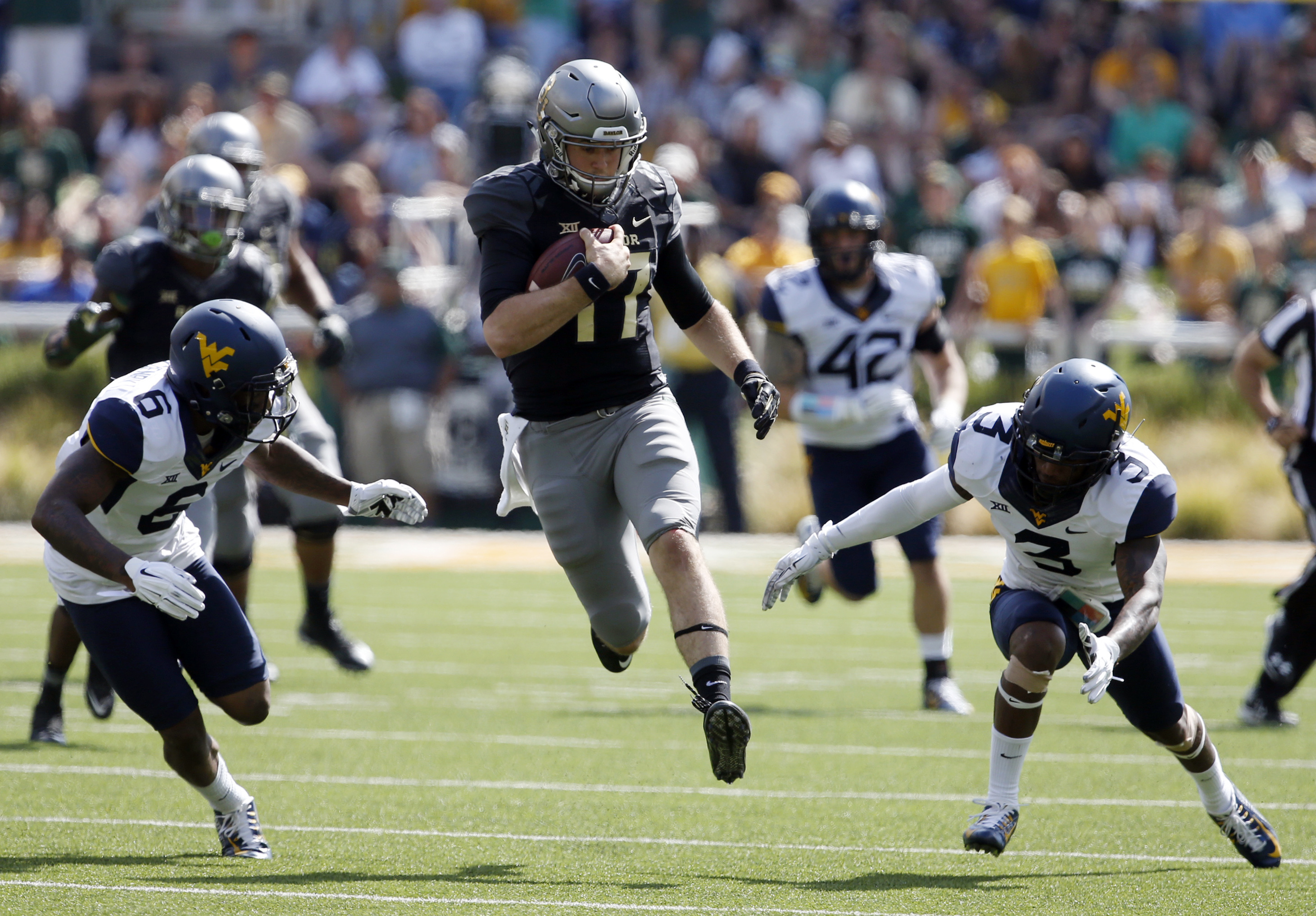 Baylor quarterback Seth Russell, center, runs between West Virginia safety Dravon Askew-Henry, left and Rick Rumph III, right, in the second half of an NCAA college football game, Saturday, Oct 17, 2015, in Waco, Texas. (AP Photo/Rod Aydelotte)