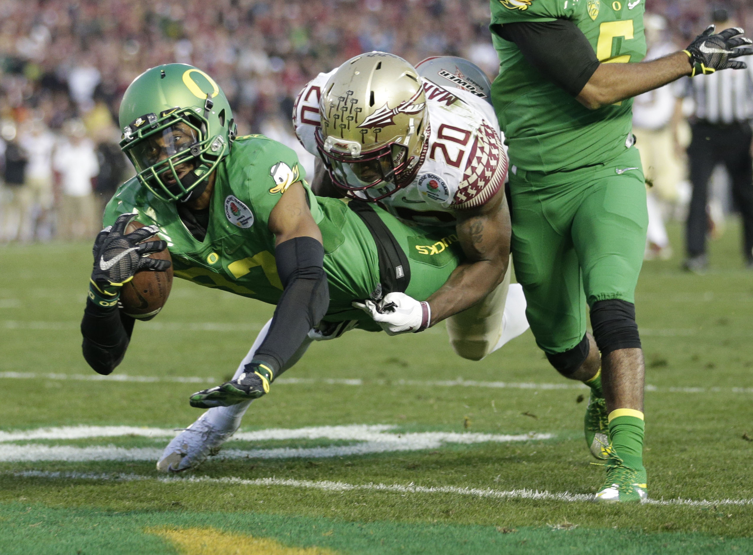 Oregon wide receiver Darren Carrington, scores under pressure by Florida State defensive back Trey Marshall during the second half of the Rose Bowl NCAA college football playoff semifinal, Thursday, Jan. 1, 2015 in Pasadena, Calif. (AP Photo/Jae C. Hong)