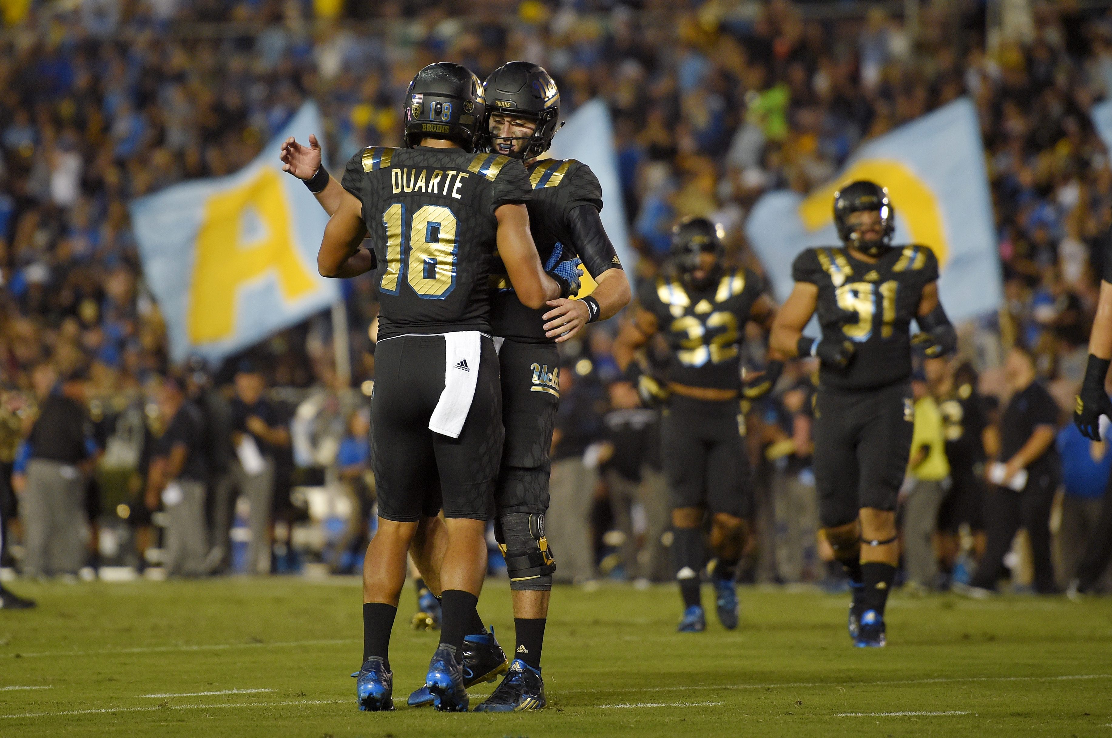UCLA wide receiver Thomas Duarte, left, is congratulated by quarterback Josh Rosen after making a touchdown catch during the first half of an NCAA college football game against California, Thursday, Oct. 22, 2015, in Pasadena, Calif. (AP Photo/Mark J. Ter