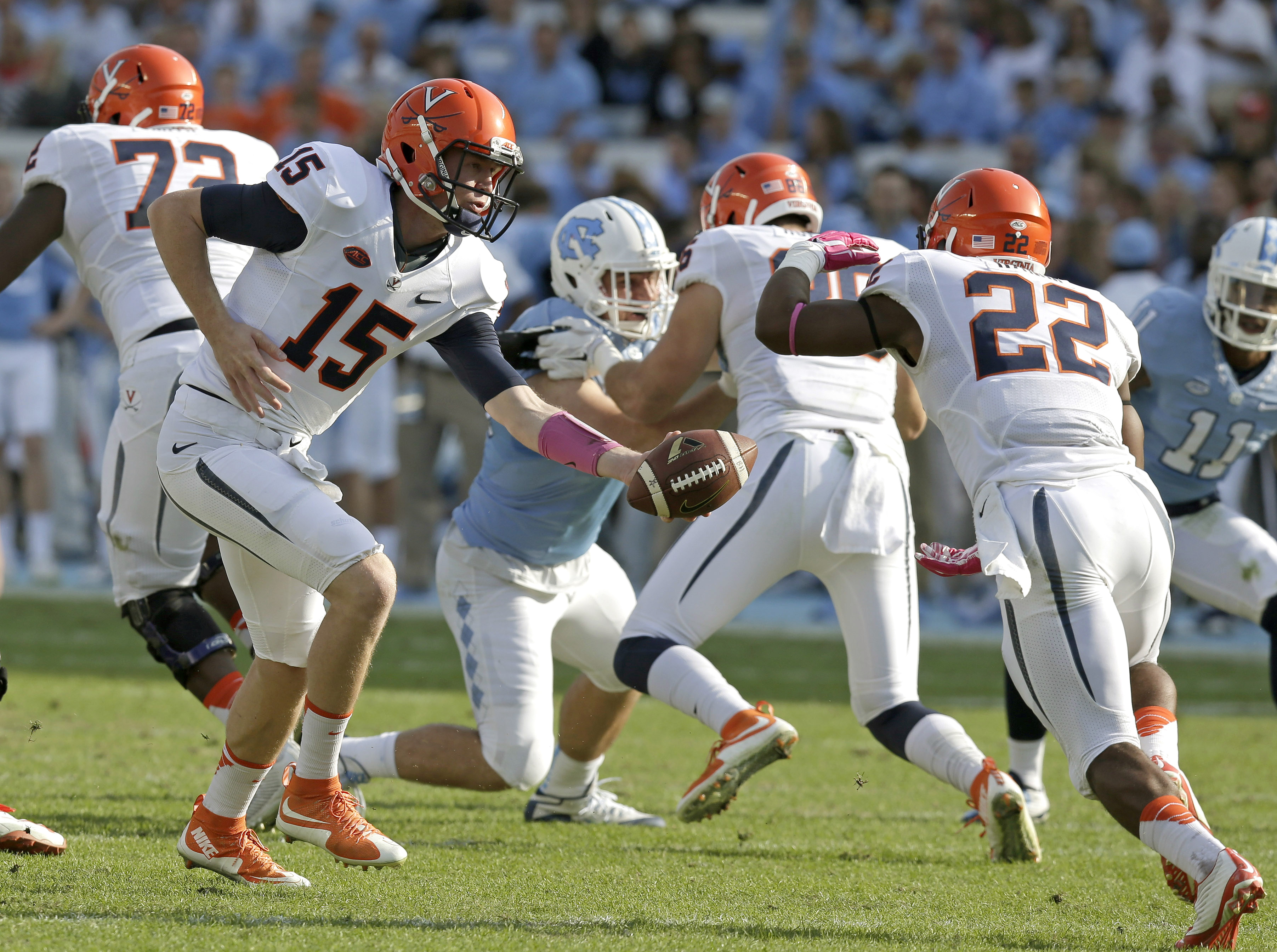 Virginia quarterback Matt Johns (15) hands off to Daniel Hamm (22) during the first half of an NCAA college football game against North Carolina in Chapel Hill, N.C., Saturday, Oct. 24, 2015. (AP Photo/Gerry Broome)