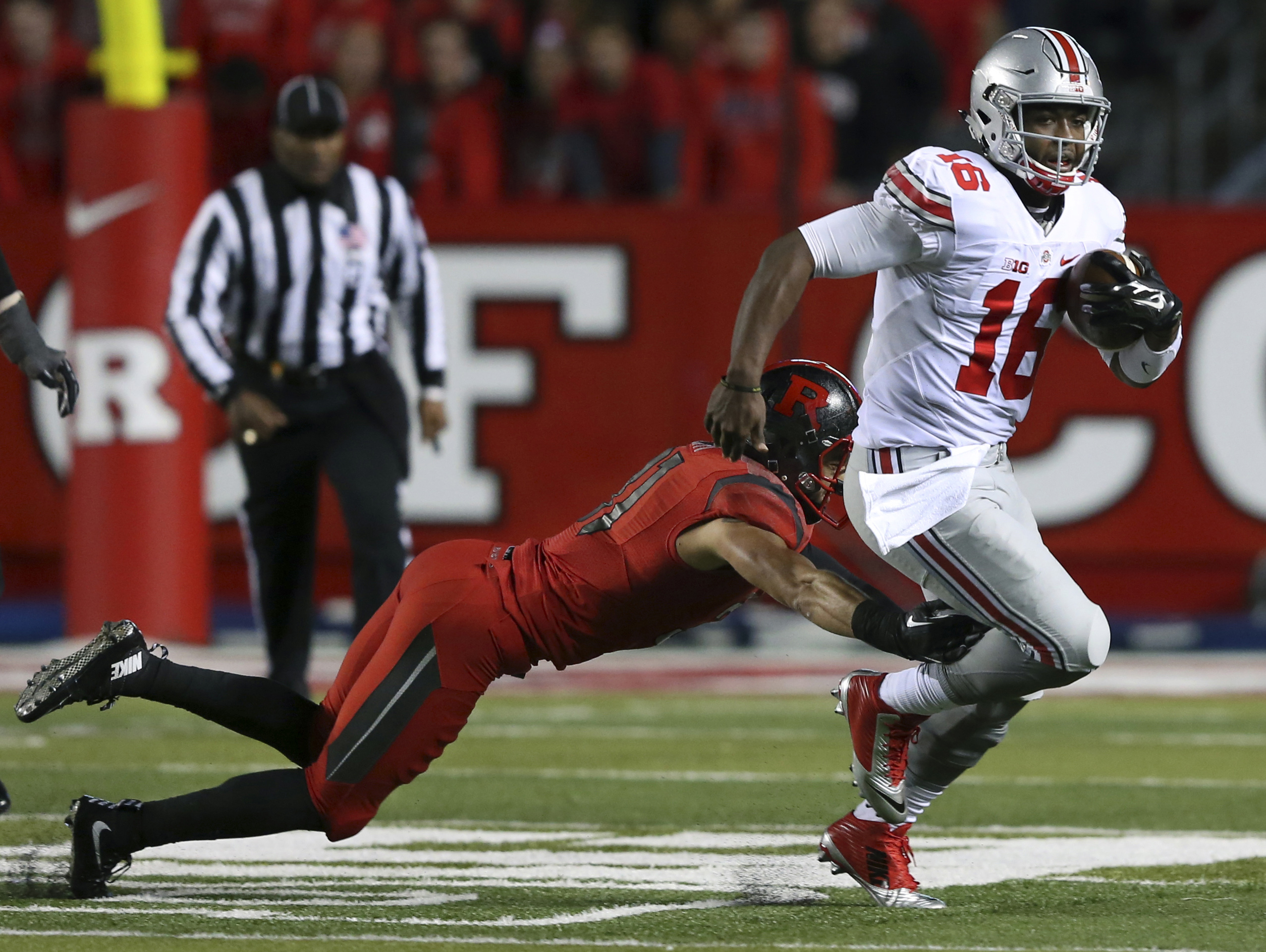 Ohio State quarterback J.T. Barrett (16) breaks a tackle by Rutgers defensive back Anthony Cioffi (31) during the first half of an NCAA college football game Saturday, Oct. 24, 2015, in Piscataway, N.J. (AP Photo/Mel Evans)