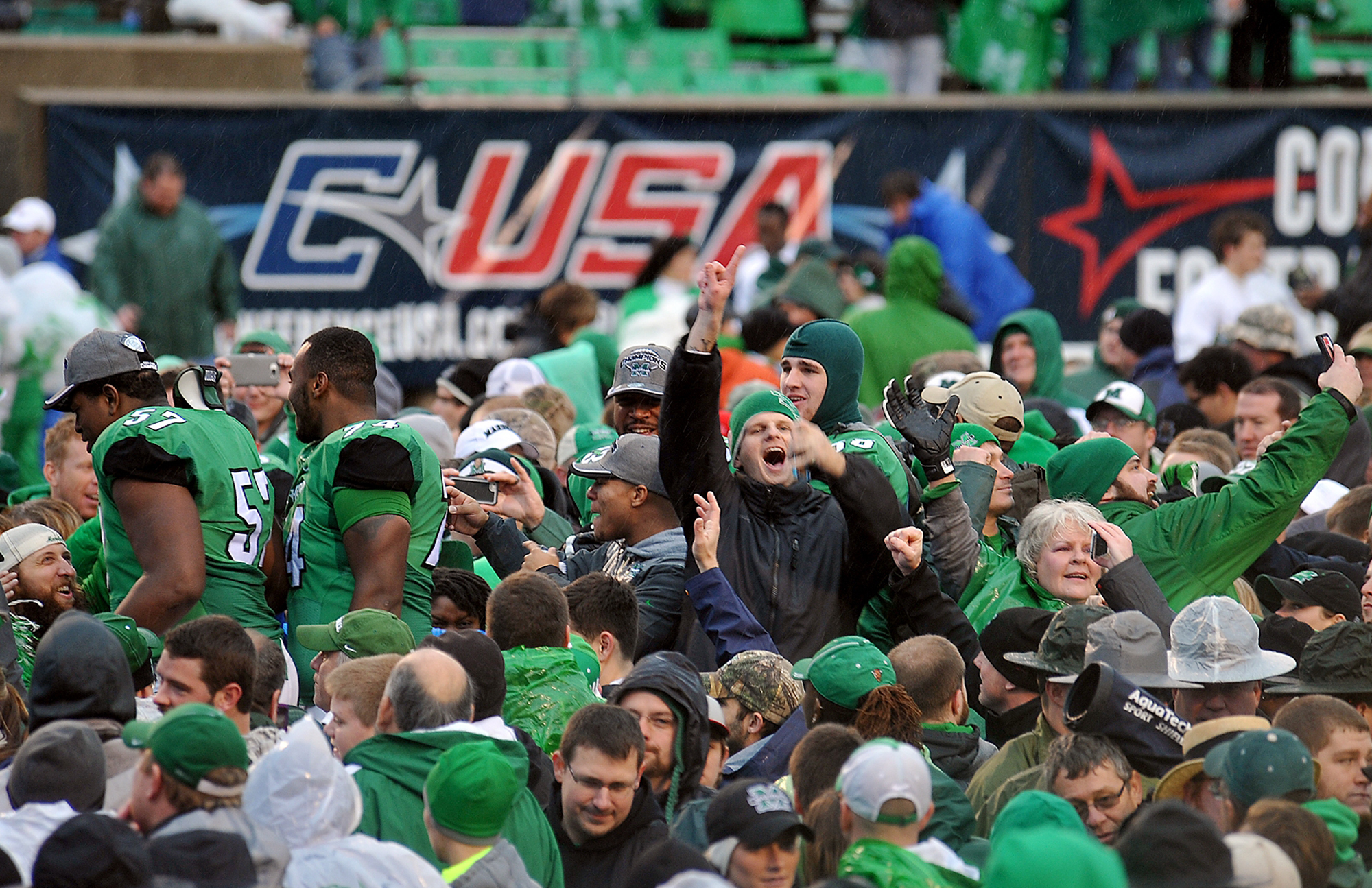 Marshall fans celebrate on the field after the school's 26-23 win over Louisiana Teach in the Conference USA championship NCAA college football game in Huntington, W.Va., Saturday Dec. 6, 2014. (AP Photo/Chris Tilley)