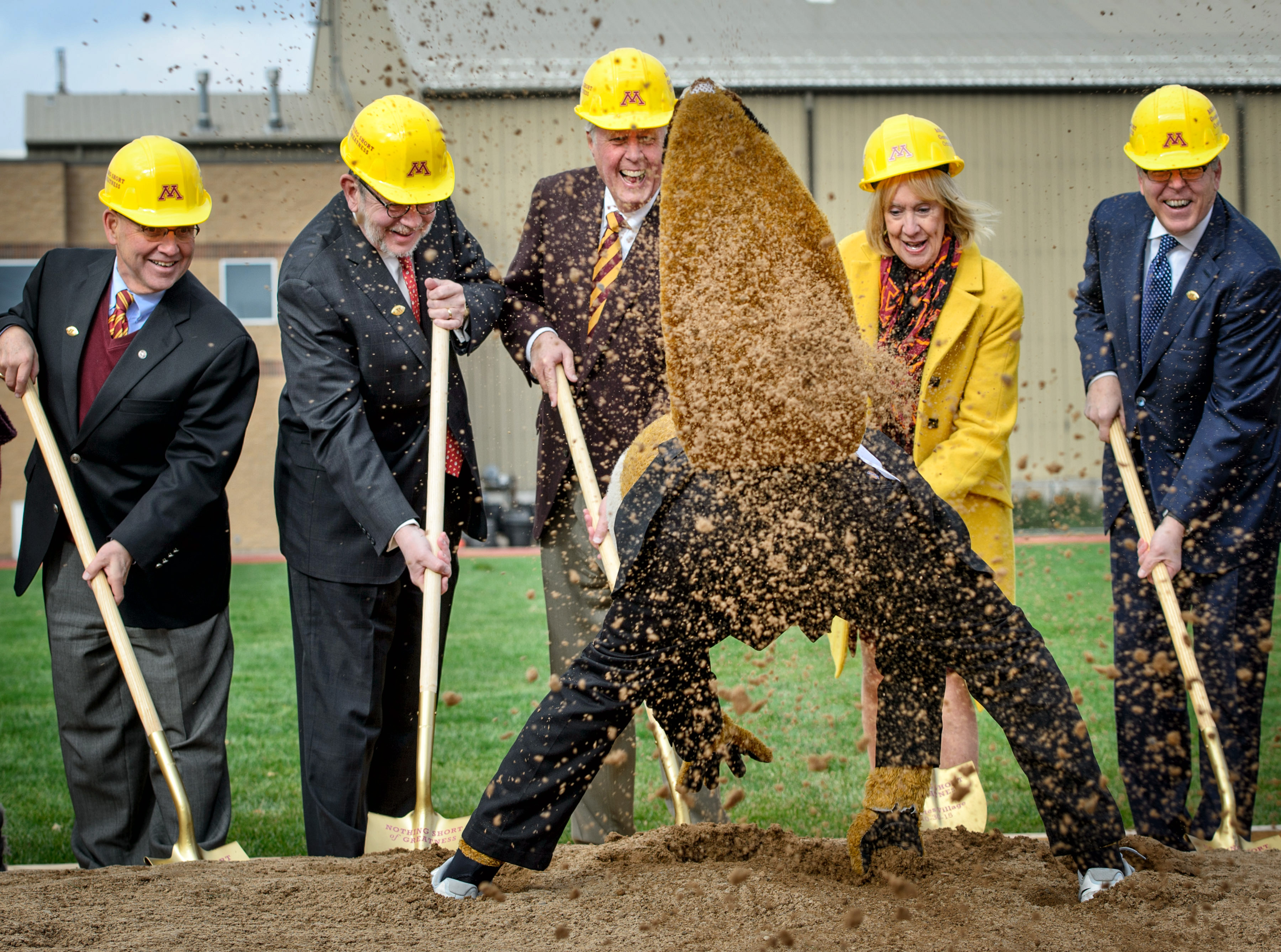 """University of Minnesota mascot """"Goldy Gopher"""" throws dirt towards photographers at groundbreaking ceremonies for the """"athletes village"""" Friday, Oct. 30, 2015, at the University of Minnesota in Minneapolis. From left, taking part in the ceremonies are rege"""
