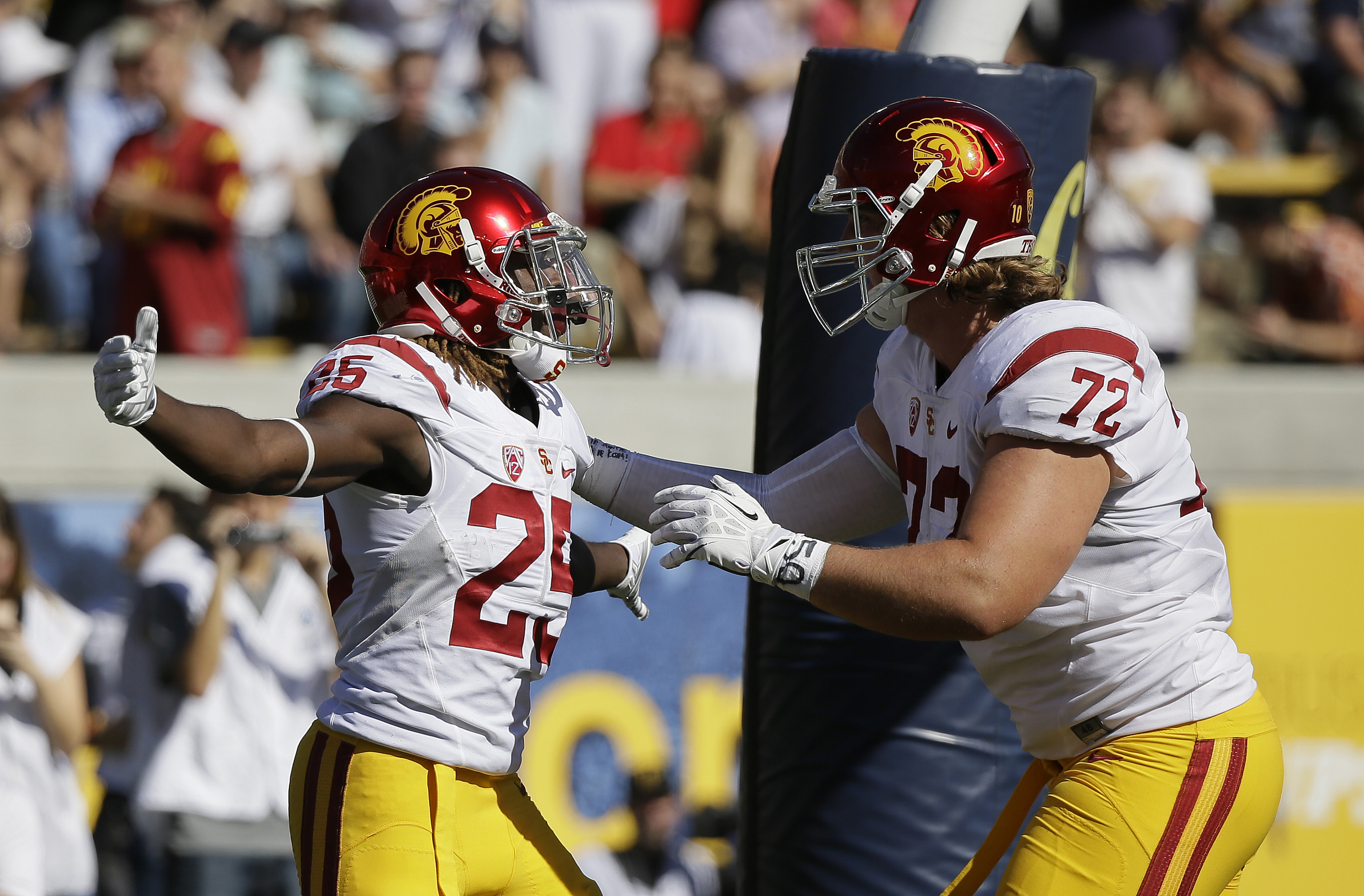 Southern California running back Ronald Jones II, left, is greeted by teammate Chad Wheeler, right, after scoring a touchdown during the first half of an NCAA college football game against California, Saturday, Oct. 31, 2015, in Berkeley, Calif. (AP Photo