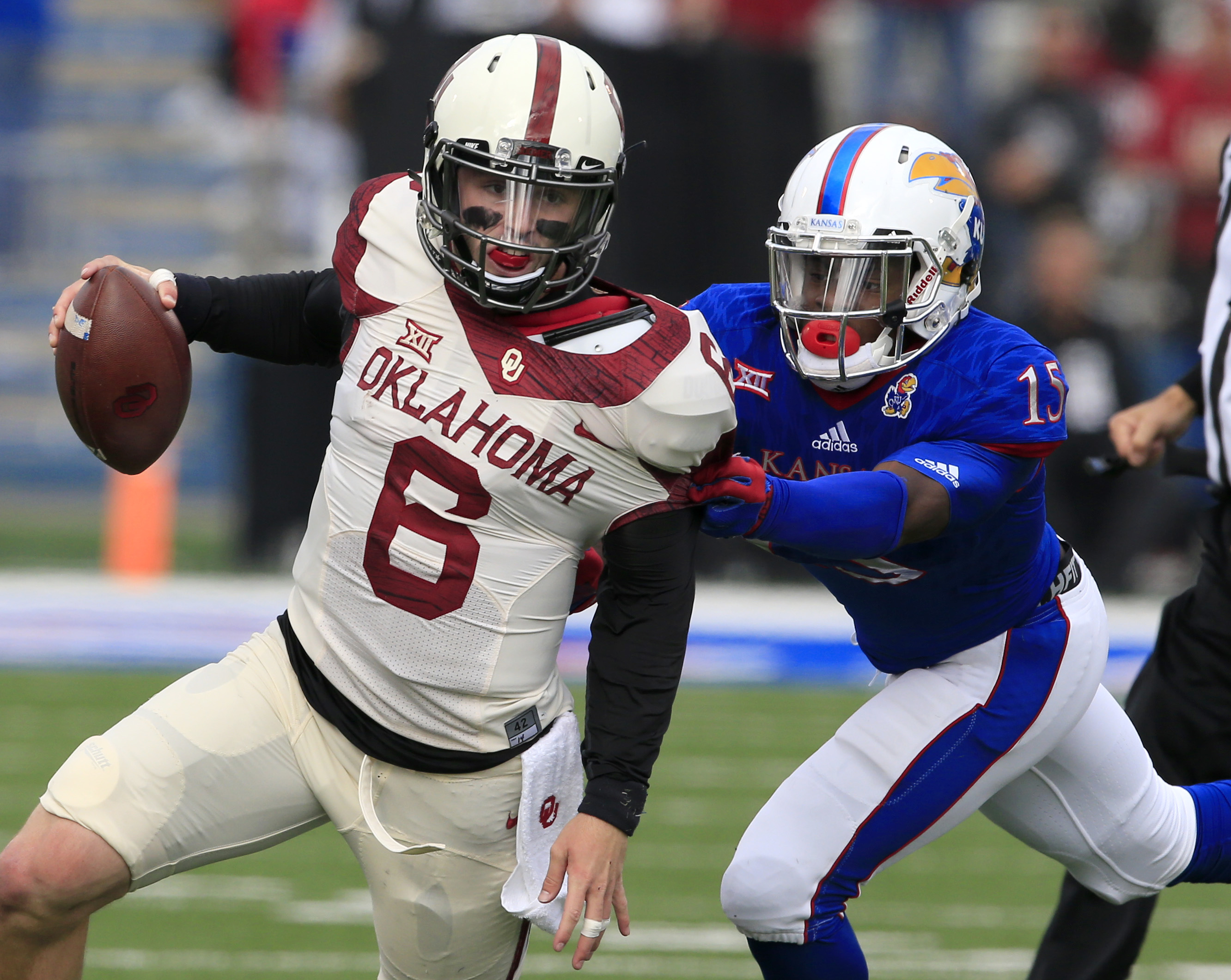 Oklahoma quarterback Baker Mayfield (6) gets away from Kansas cornerback Chevy Graham (15) during the first half of an NCAA college football game in Lawrence, Kan., Saturday, Oct. 31, 2015. (AP Photo/Orlin Wagner)