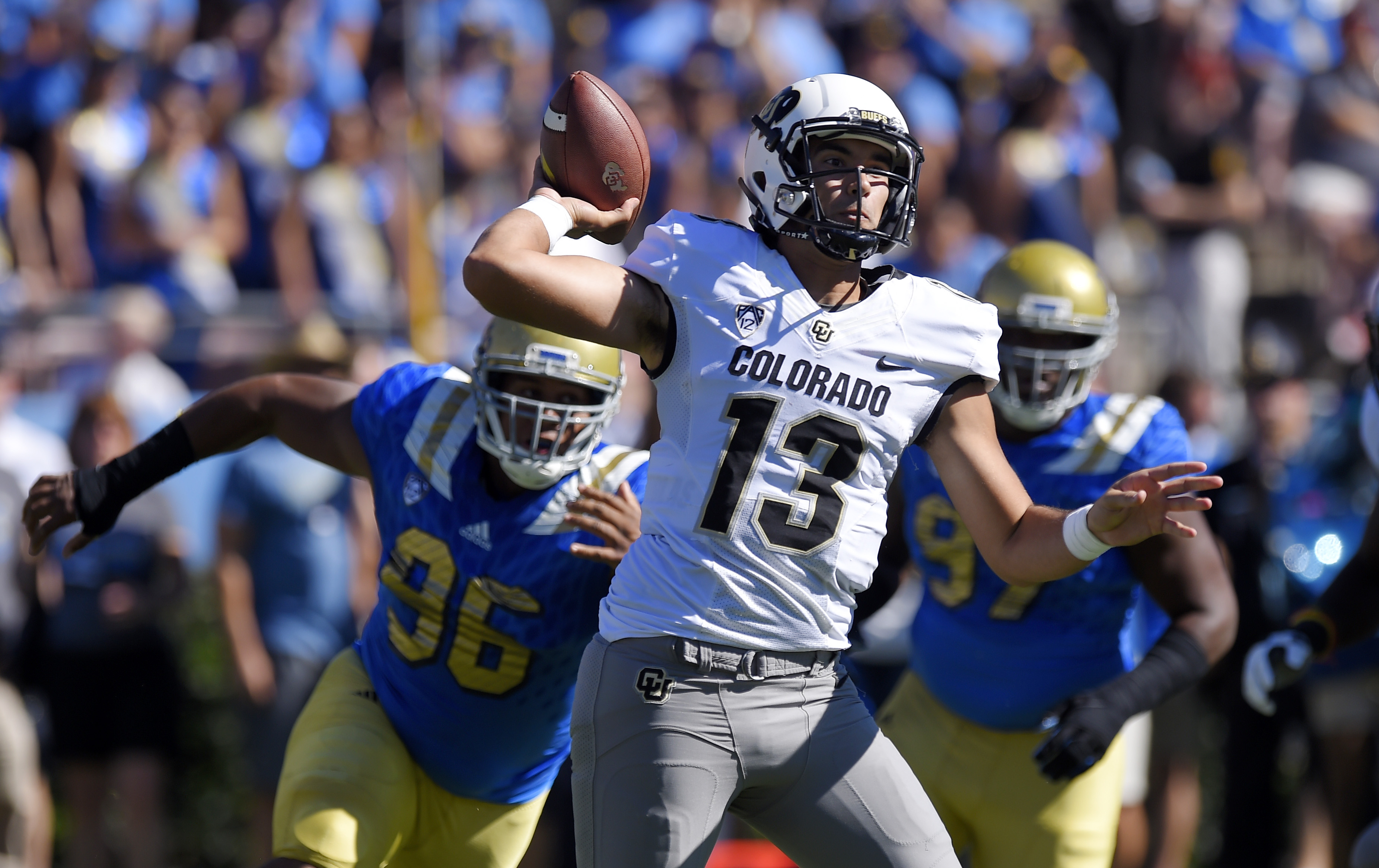 Colorado quarterback Sefo Liufau, center, passes under pressure from UCLA defensive lineman Eli Ankou, left, during the first half of an NCAA college football game, Saturday, Oct. 31, 2015, in Pasadena, Calif. (AP Photo/Mark J. Terrill)