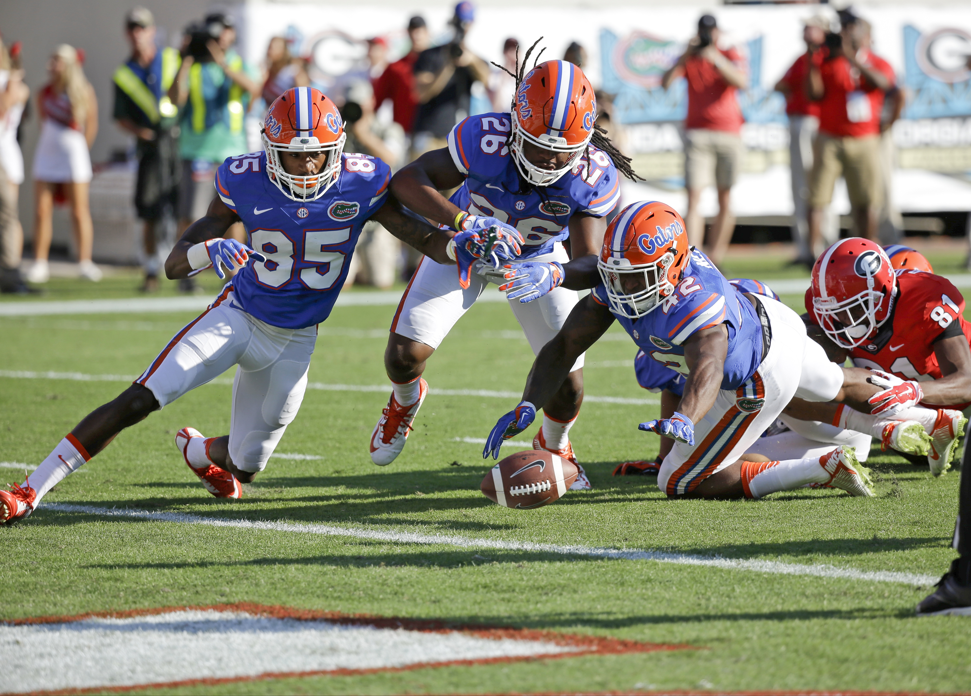 Florida players Chris Thompson (85), Marcell Harris (26) and Keanu Neal (42) go after a fumbled fair catch by Georgia's Reggie Davis (81) during the first half of an NCAA college football game  Saturday, Oct. 31, 2015, in Jacksonville, Fla.  Florida's Nic