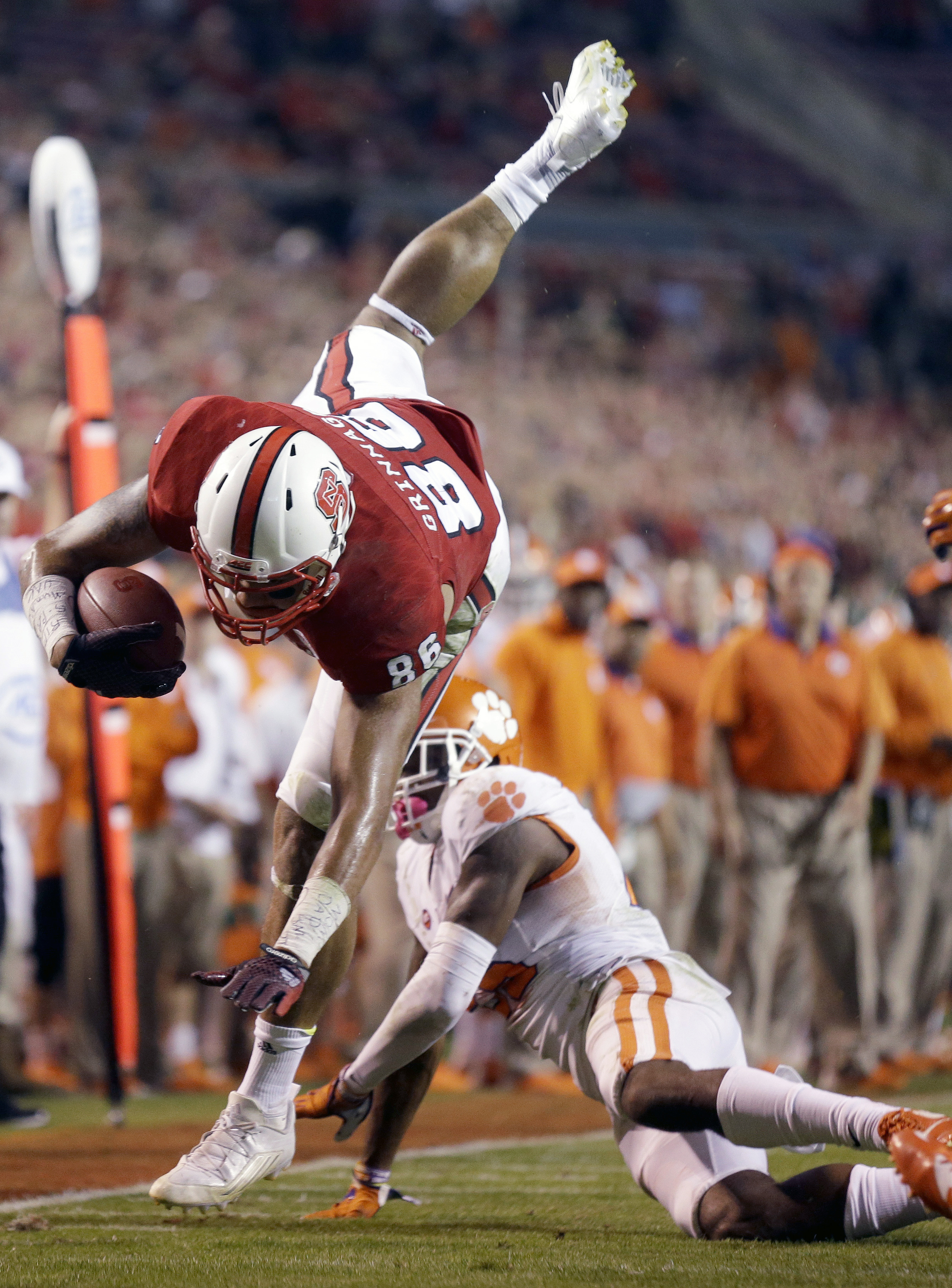Clemson's Cordrea Tankersley, right, upends North Carolina State's David J. Grinnage (86) during the second half of an NCAA college football game in Raleigh, N.C., Saturday, Oct. 31, 2015. Clemson won 56-41. (AP Photo/Gerry Broome)