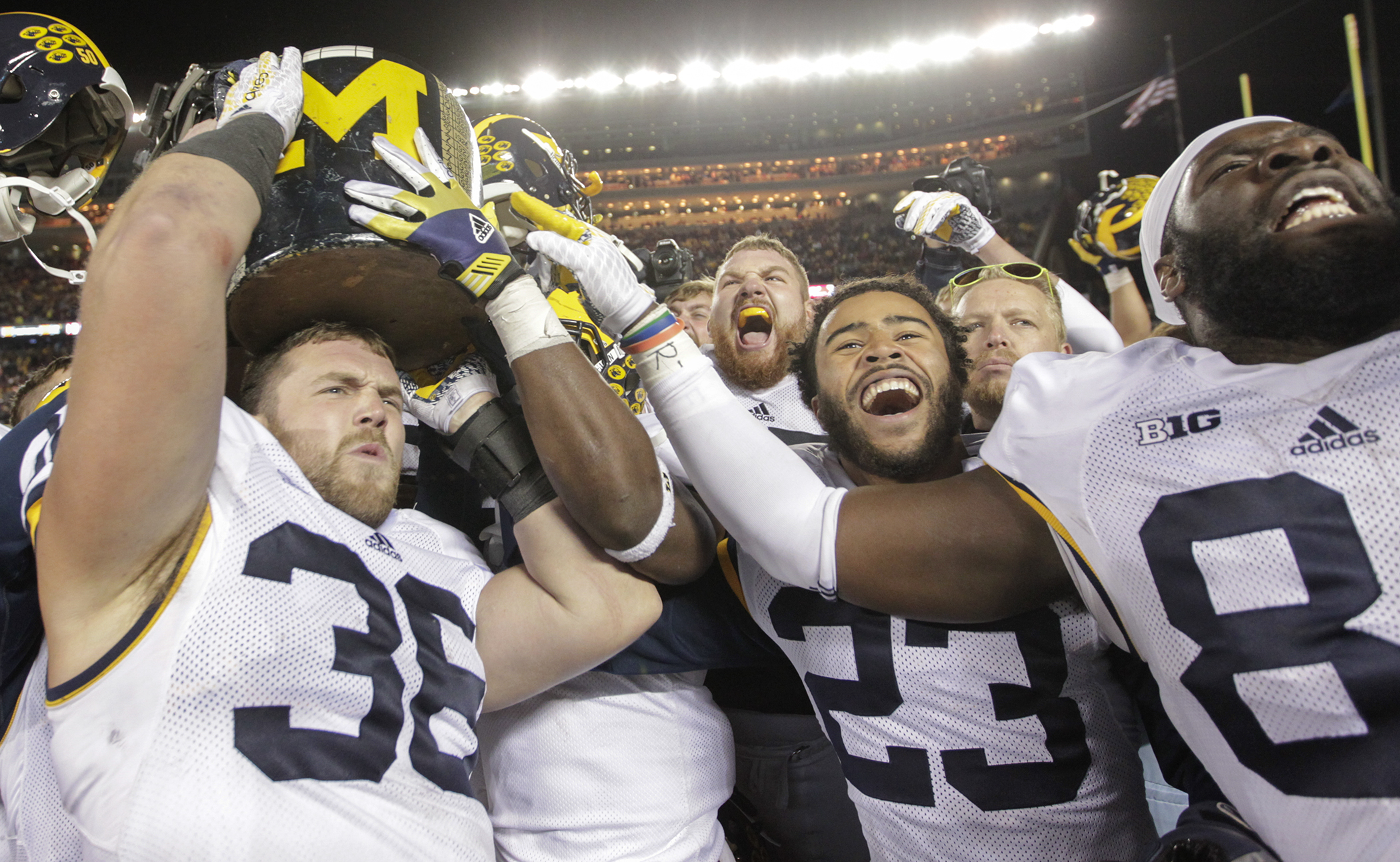 Michigan's Joe Kerridge (36), Jordan Glasgow (23) and A.J. Williams (84) carry the Little Brown Jug off the field after beating Minnesota 29-26 in an NCAA college football game Saturday, Oct. 31, 2015, in Minneapolis.(AP Photo/Paul Battaglia)