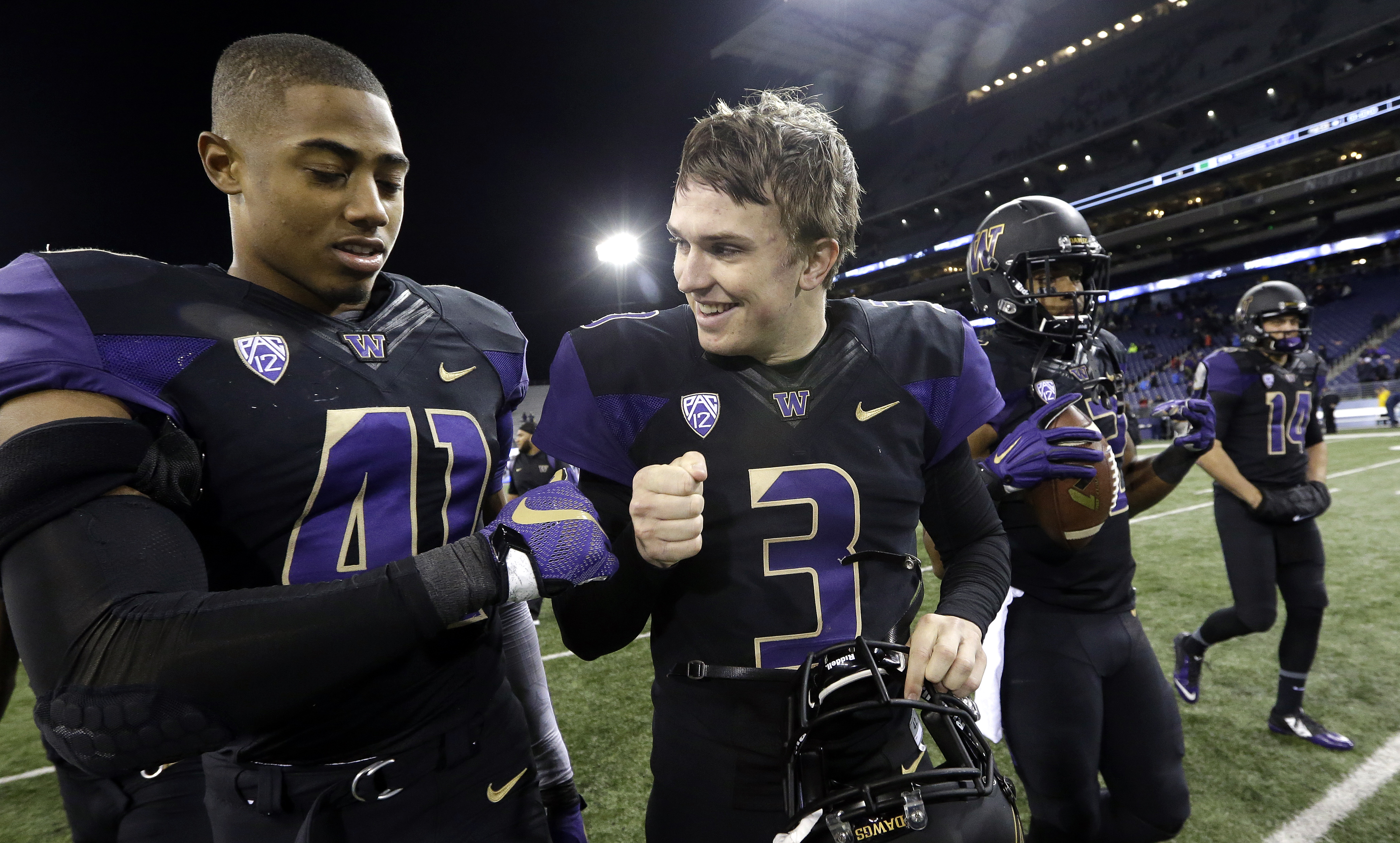 Washington quarterback Jake Browning (3) smiles as he walks off the field with Travis Feeney after an NCAA college football game against Arizona on Saturday, Oct. 31, 2015, in Seattle. Washington won 49-3. (AP Photo/Elaine Thompson)
