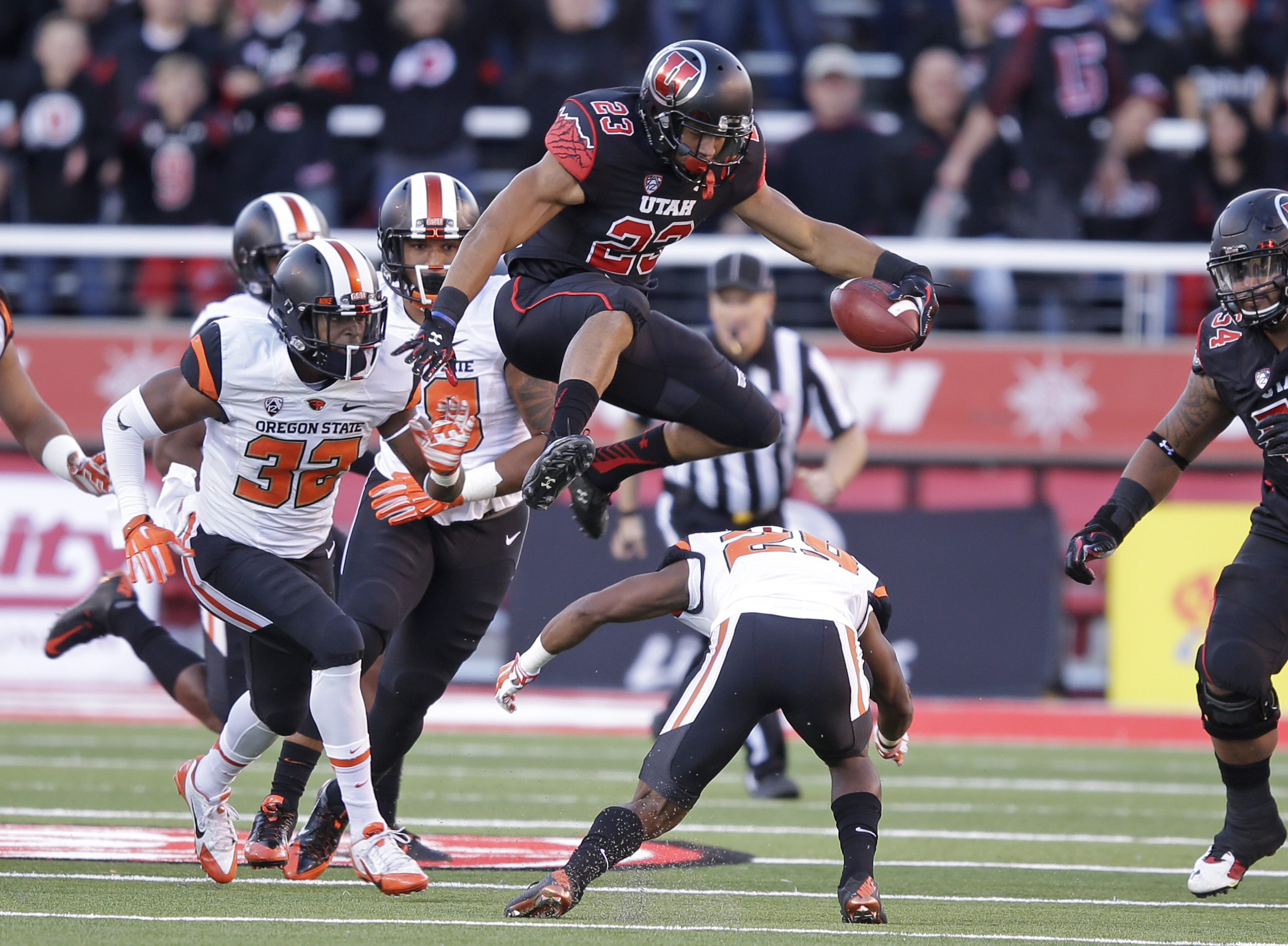 FILE - This Saturday, Oct. 31, 2015, file photo, shows Utah running back Devontae Booker (23) leaping over Oregon State cornerback Dwayne Williams (29) as teammate linebacker Jonathan Willis (32) pursues in the first quarter during an NCAA college footbal