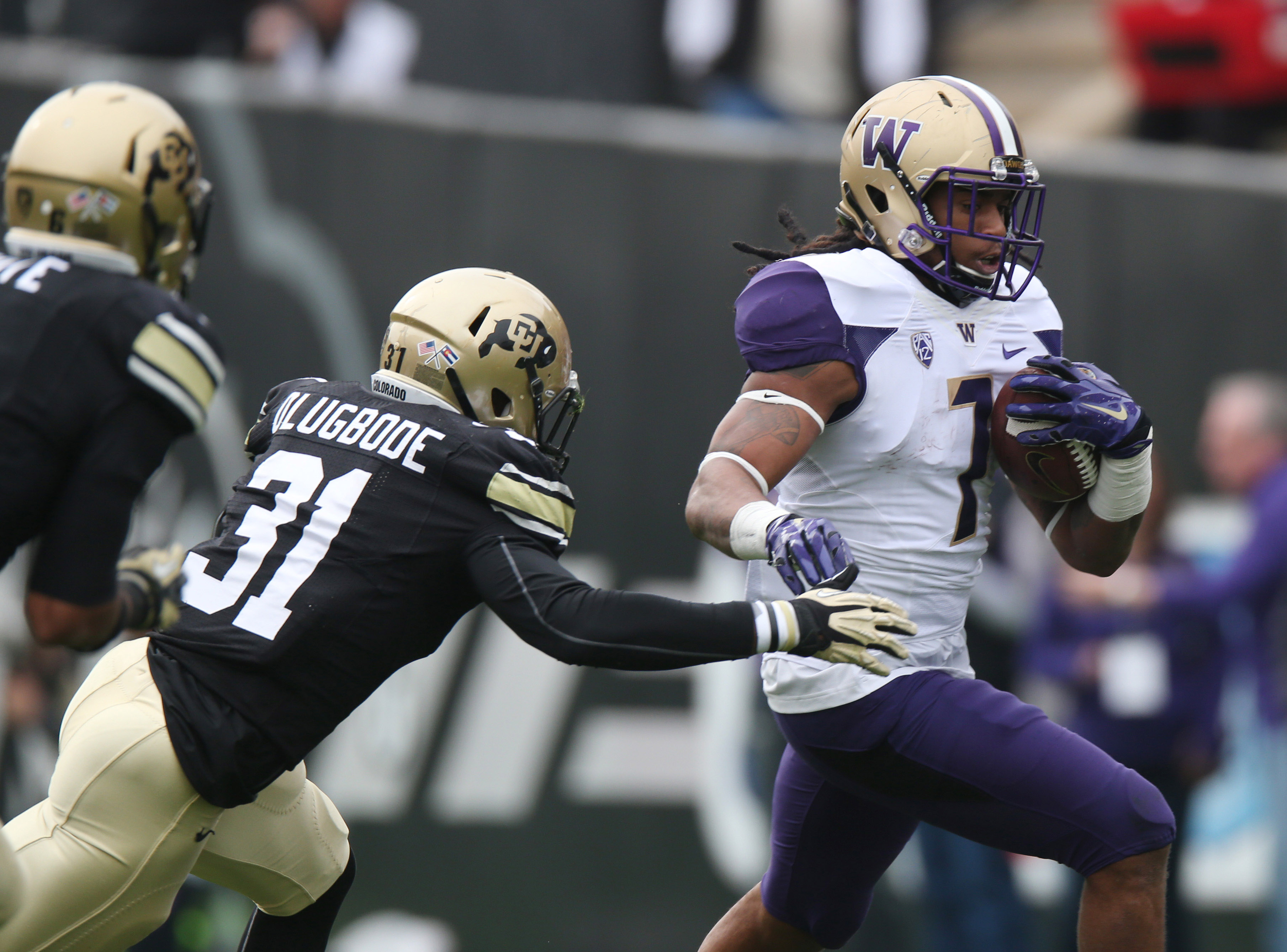In this Saturday, Nov. 1, 2014, photo, Washington running back Shaq Thompson, right, eludes a tackle attempt by Colorado linebacker Kenneth Olugbode during an NCAA college football game in Boulder, Colo. Olugbode will be back on the gridiron when Colorado