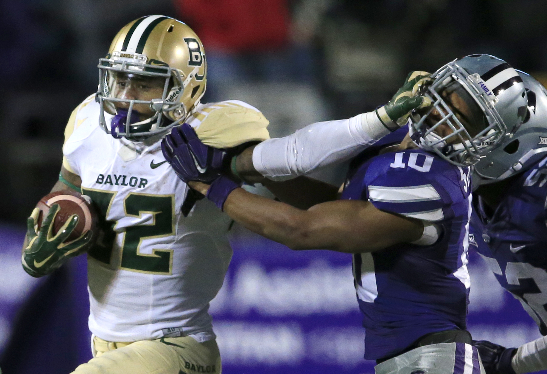 Baylor running back Shock Linwood (32) stiff-arms Kansas State defensive back Donnie Starks (10) during the second half of an NCAA college football game in Manhattan, Kan., Thursday, Nov. 5, 2015. Baylor defeated Kansas State 31-24. (AP Photo/Orlin Wagner