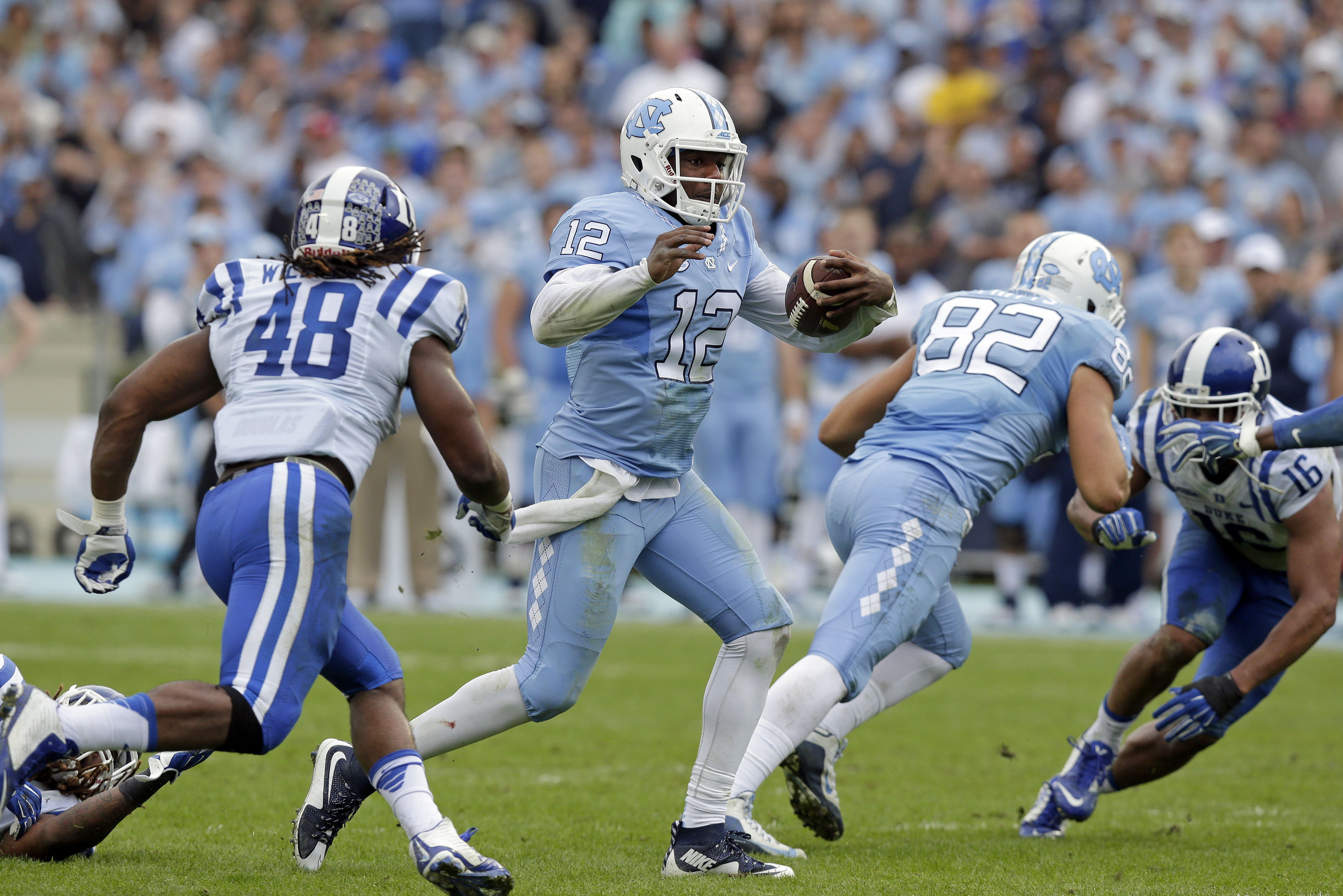 North Carolina quarterback Marquise Williams (12)  finds some running room as Duke's Deion Williams (48) looks for the tackle during the first half of an NCAA college football game in Chapel Hill, N.C., Saturday, Nov. 7, 2015. (AP Photo/Gerry Broome)