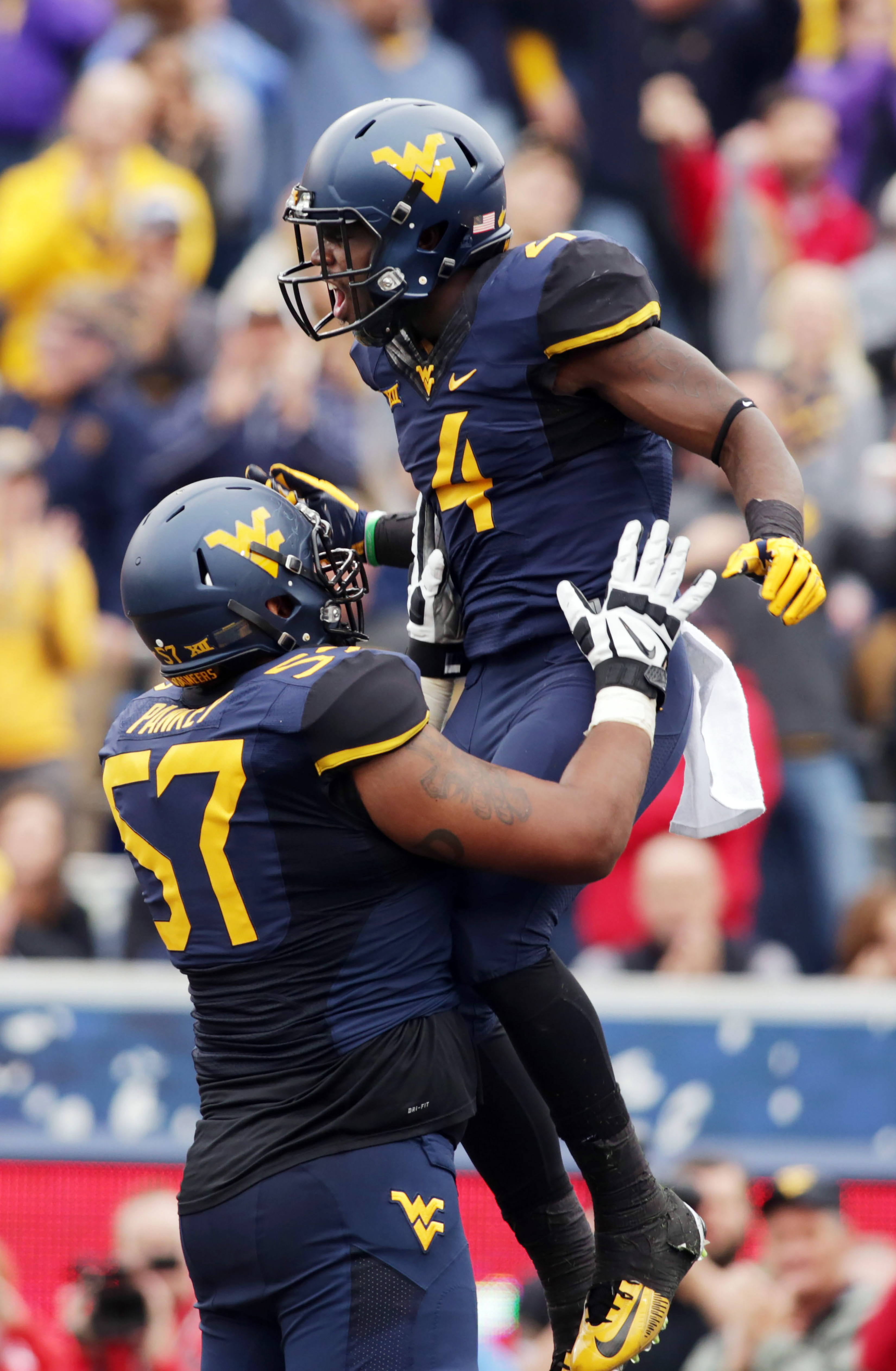 West Virginia offensive lineman Adam Pankey (57) picks up running back Wendell Smallwood (4) after he scored a touchdown during the first half of an NCAA college football game against Texas Tech, Saturday, Nov. 7, 2015, in Morgantown, W.Va. (AP Photo/Raym