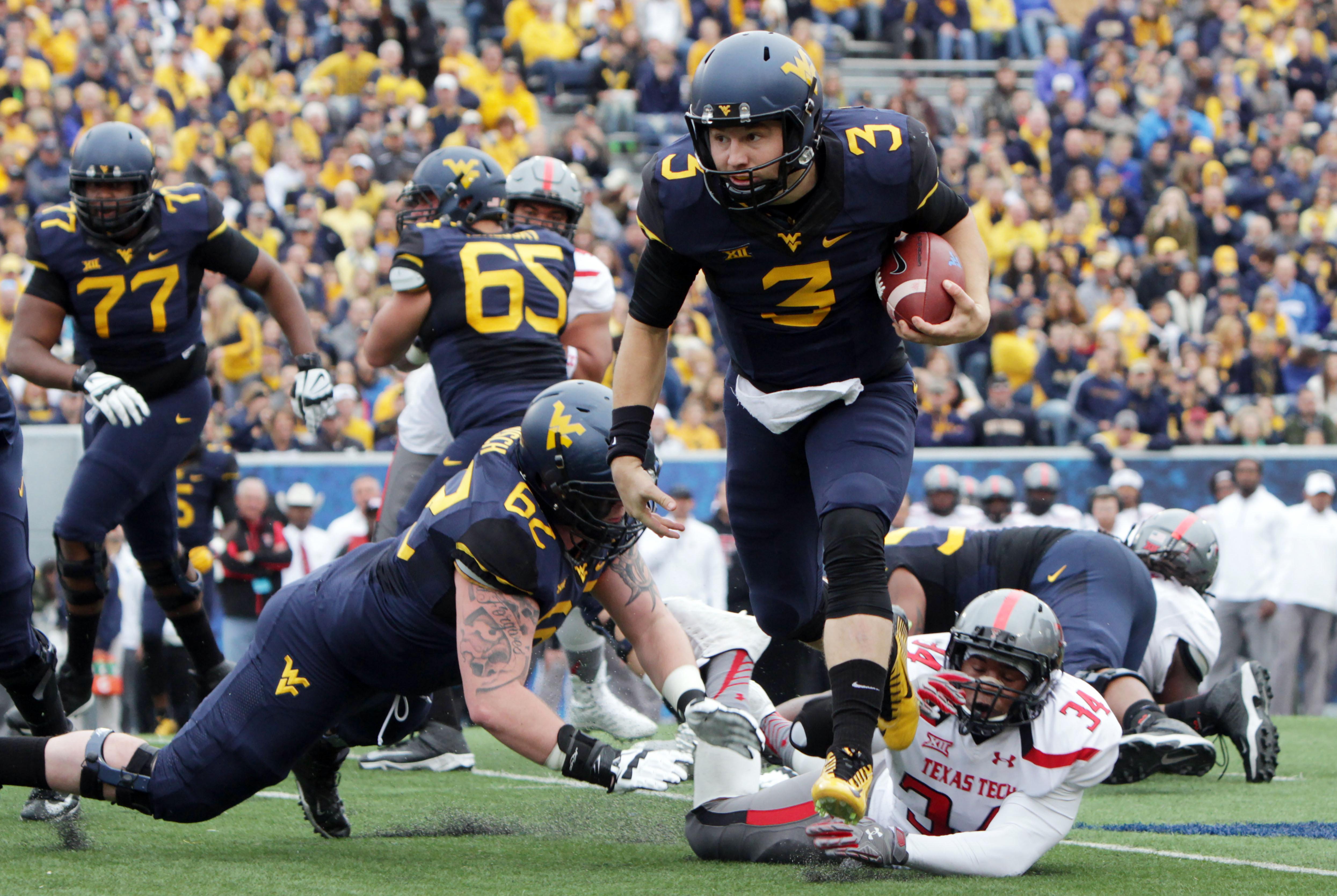 West Virginia quarterback Skyler Howard (3) avoids Texas Tech linebacker D'Vonta Hinton (34)  during the first half of an NCAA college football game, Saturday, Nov. 7, 2015, in Morgantown, W.Va. (AP Photo/Raymond Thompson)