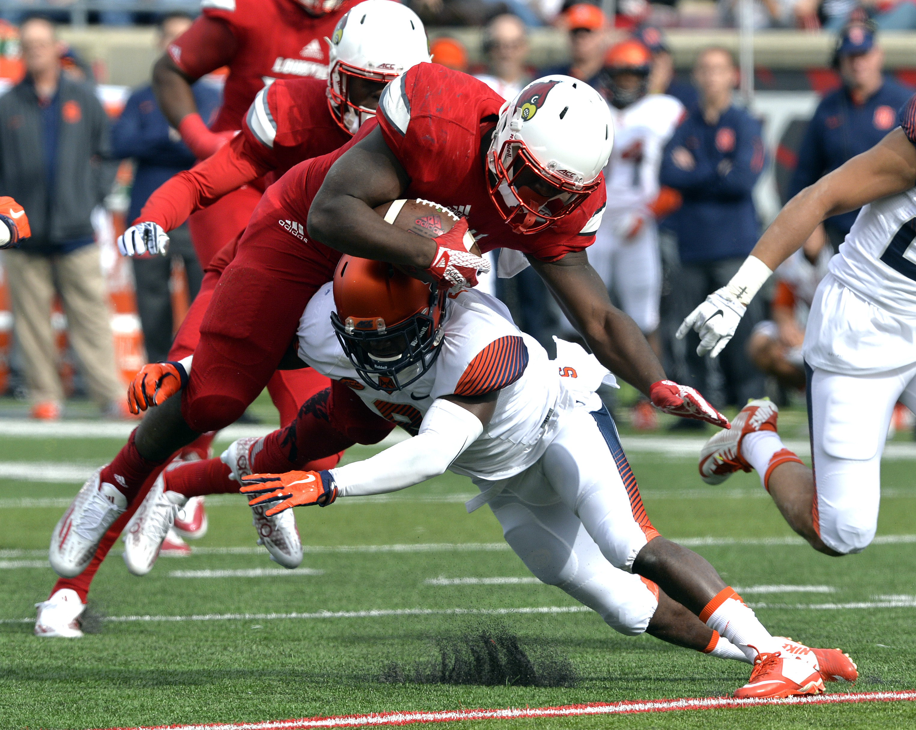 Louisville running back Jeremy Smith, top, is hit by Syracuse safety Antwan Cordy during the first half of an NCAA college football game Saturday, Nov. 7, 2015, in Louisville, Ky. (AP Photo/Timothy D. Easley)