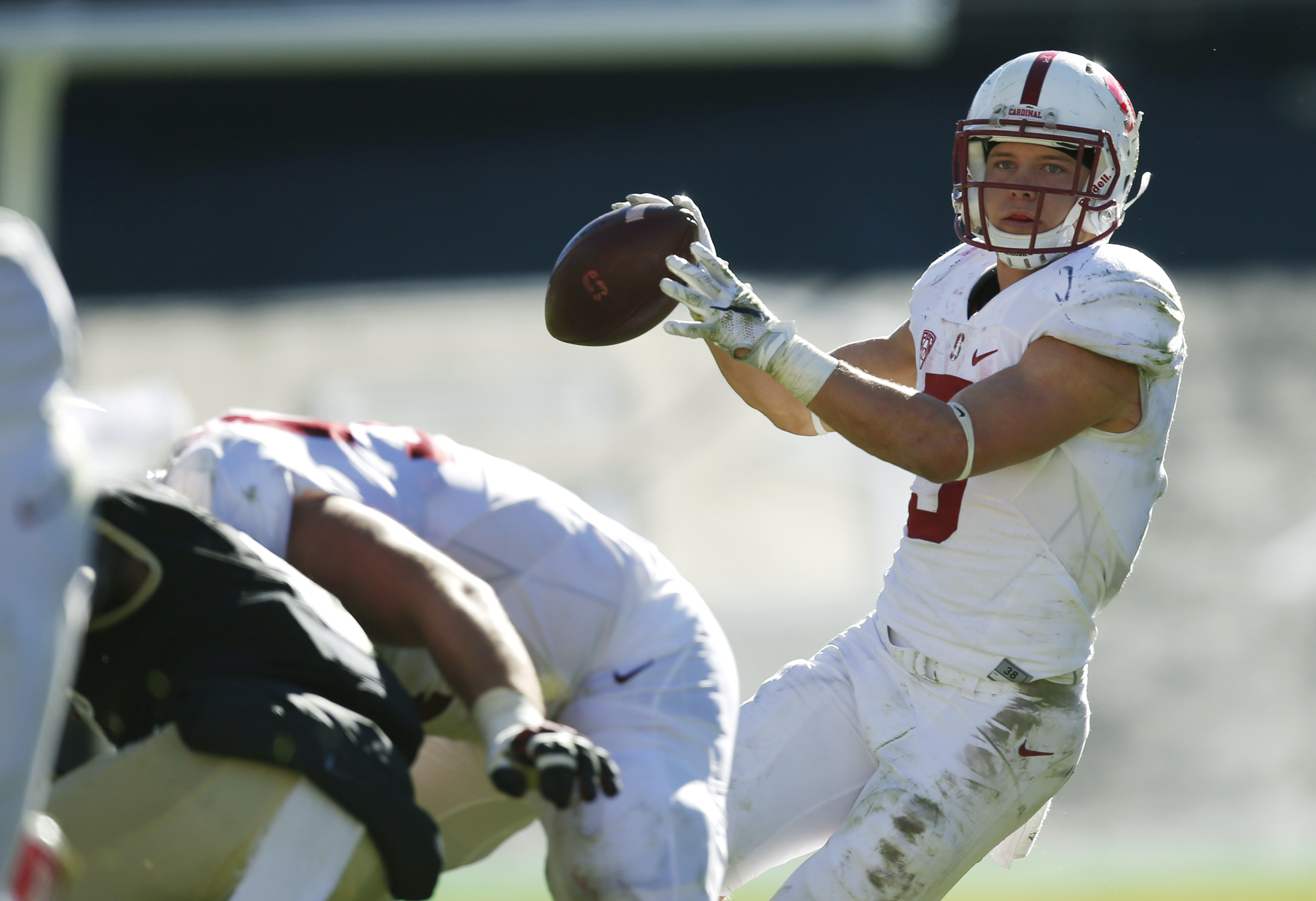 Stanford running back Christian McCaffrey, back, fades back to throw a pass for a touchdown against Colorado in the second half of an NCAA college football game Saturday, Nov. 7, 2015, in Boulder, Colo. Stanford won 42-10. (AP Photo/David Zalubowski)