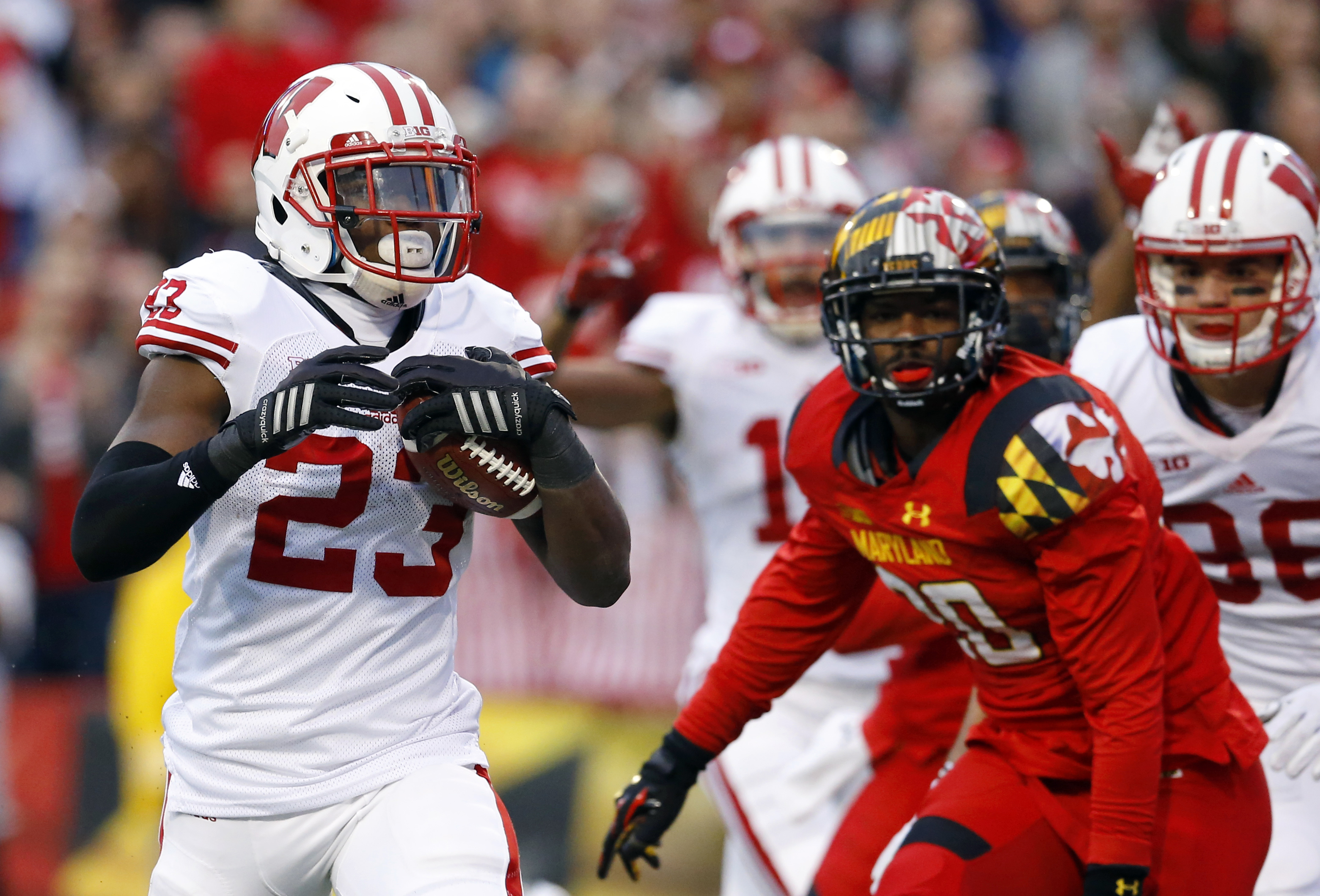Wisconsin running back Dare Ogunbowale, left, scores a touchdown in front of Maryland defensive back Anthony Nixon, back right, in the first half of an NCAA college football game, Saturday, Nov. 7, 2015, in College Park, Md. (AP Photo/Patrick Semansky)