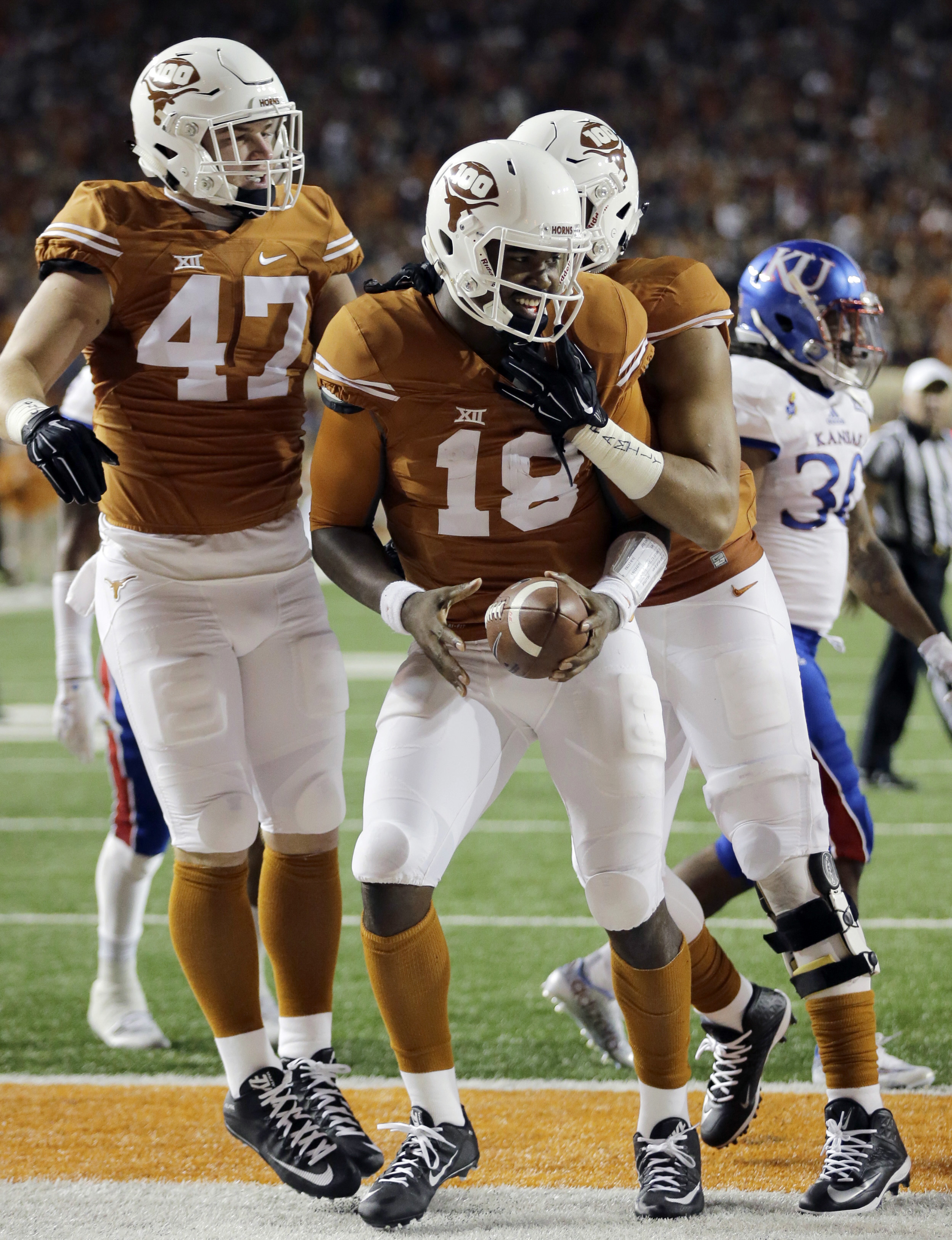 Texas quarterback Tyrone Swoopes (18) celebrates with teammates Andrew Beck (47) and Caleb Bluiett, right, after he scored a touchdown against Kansas during the first half of an NCAA college football game, Saturday, Nov. 7, 2015, in Austin, Texas. (AP Pho