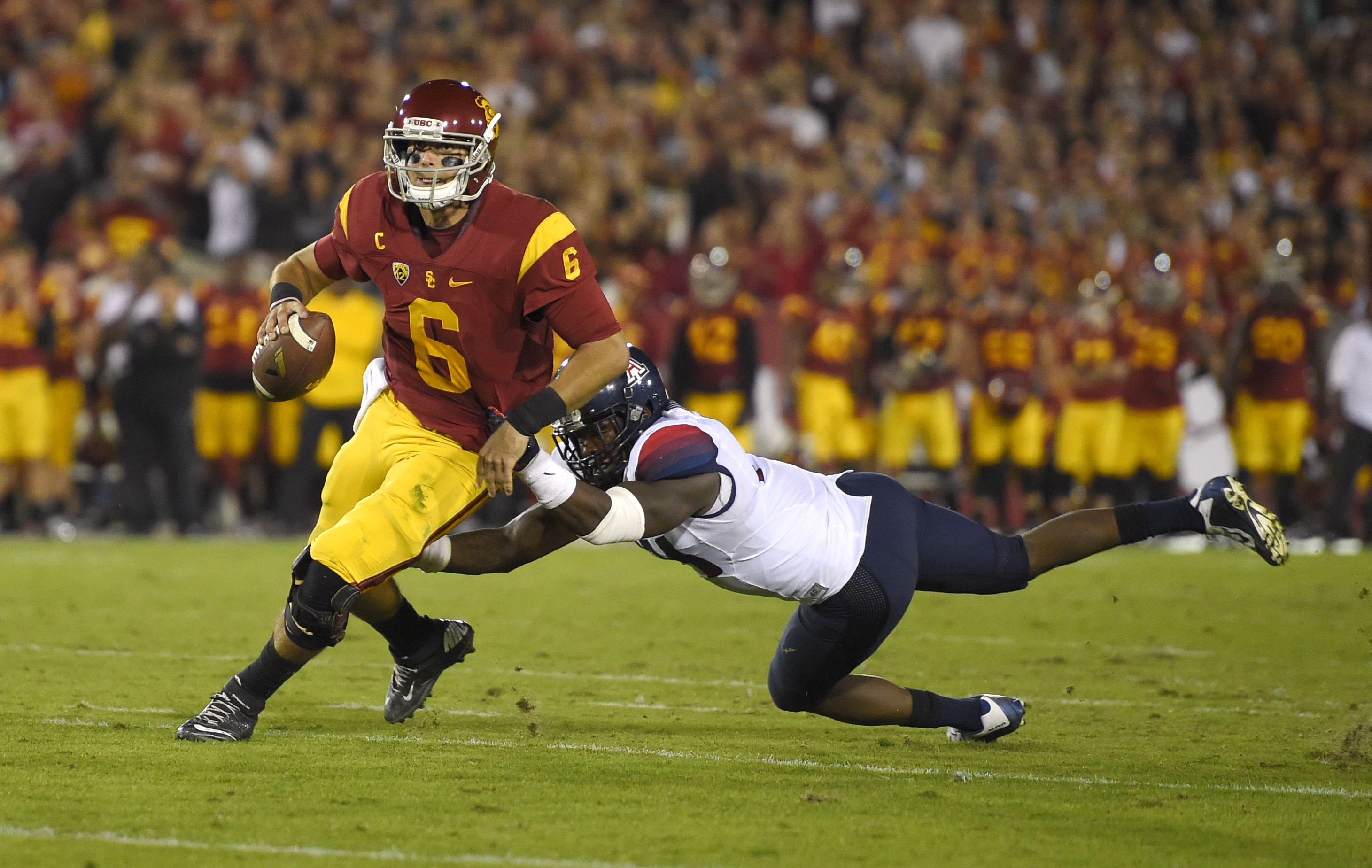 Southern California quarterback Cody Kessler, left, escapes the grasp of Arizona safety Paul Magloire Jr. during the first half of an NCAA college football game, Saturday, Nov. 7, 2015, in Los Angeles. (AP Photo/Mark J. Terrill)