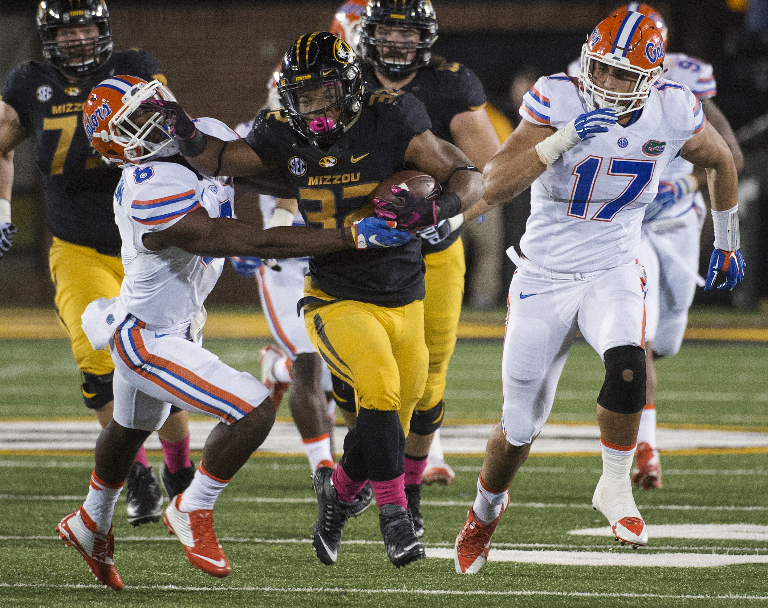 FILE - In this Oct. 10, 2015, file photo, Missouri running back Russell Hansbrough, center, fights his way past Florida's Nick Washington, left, and Jordan Sherit, right, during an NCAA college football game in Columbia, Mo. Some Missouri football players