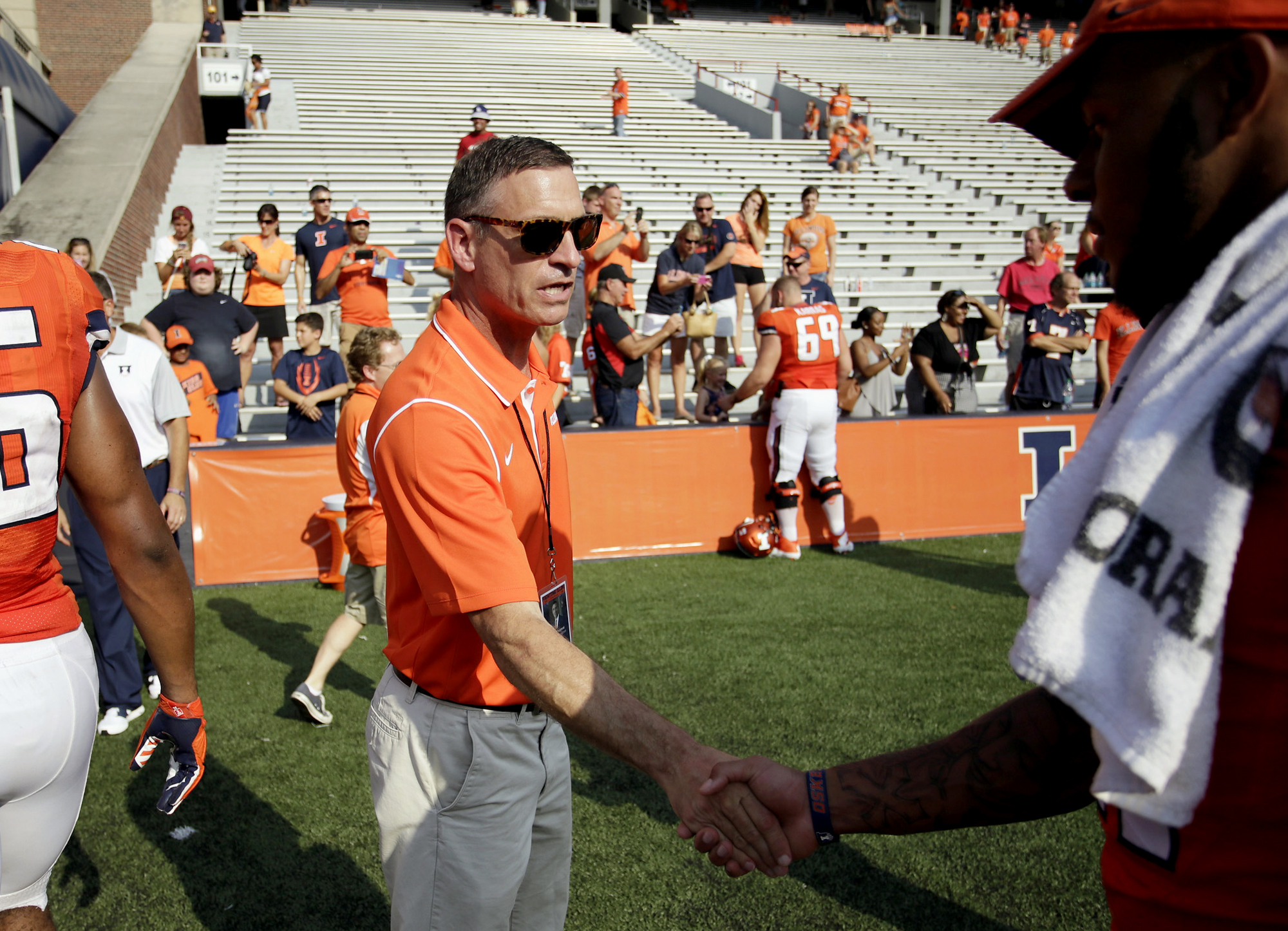 FILE - In this Sept. 5, 2015 file photo, Illinois athletic director Mike Thomas congratulates players after an NCAA college football game against in Champaign, Ill. In a motion filed Tuesday, Oct. 20, 2015, the university argues that a judge should dismis