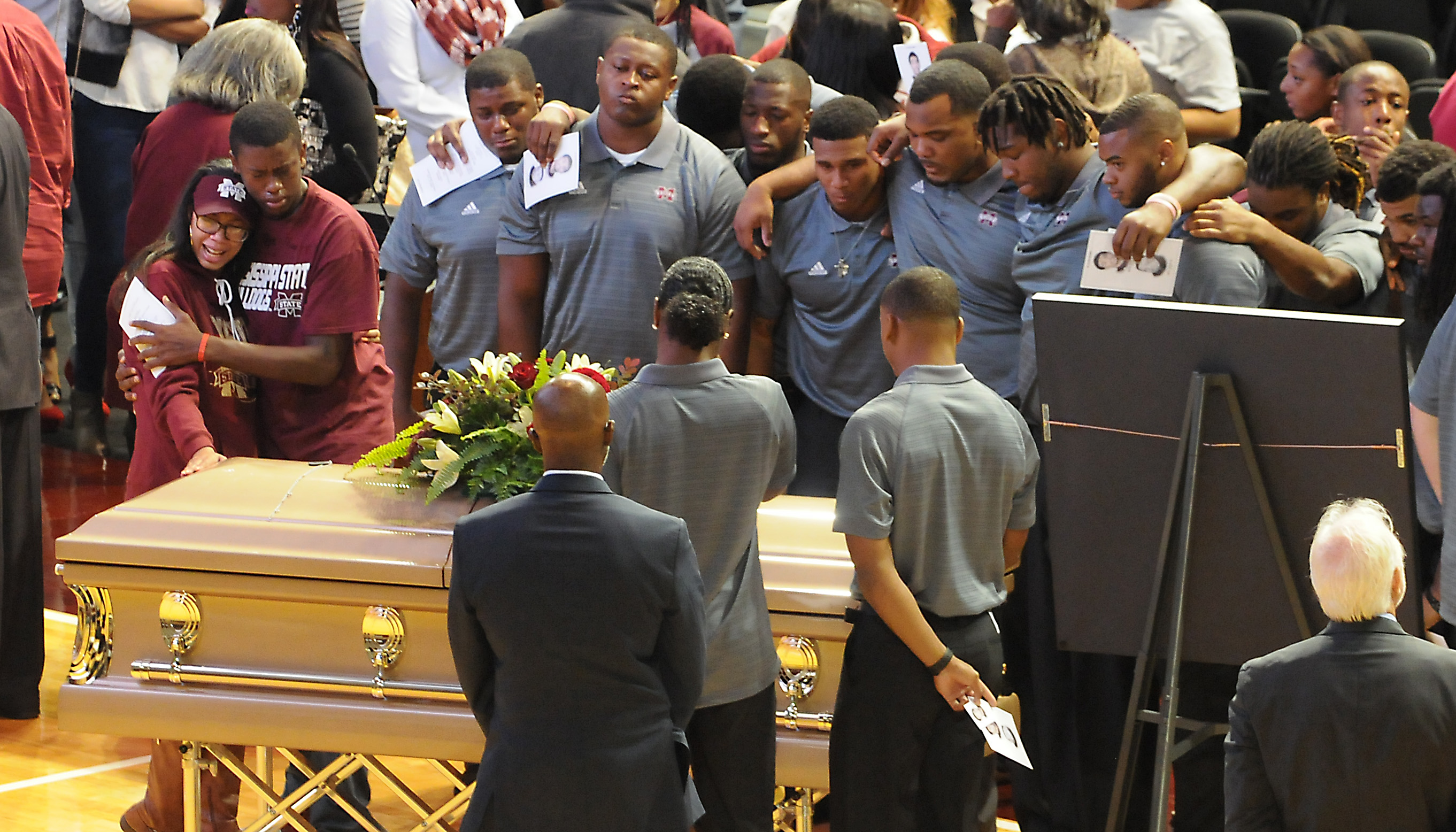 Mississippi State football team members (all in short sleeve grey shirts) gather around the casket of Keith Joseph Jr., following his memorial service at Mississippi State University on Thursday, Nov. 12, 2015,  in Starkville,  Miss. Mississippi State hos