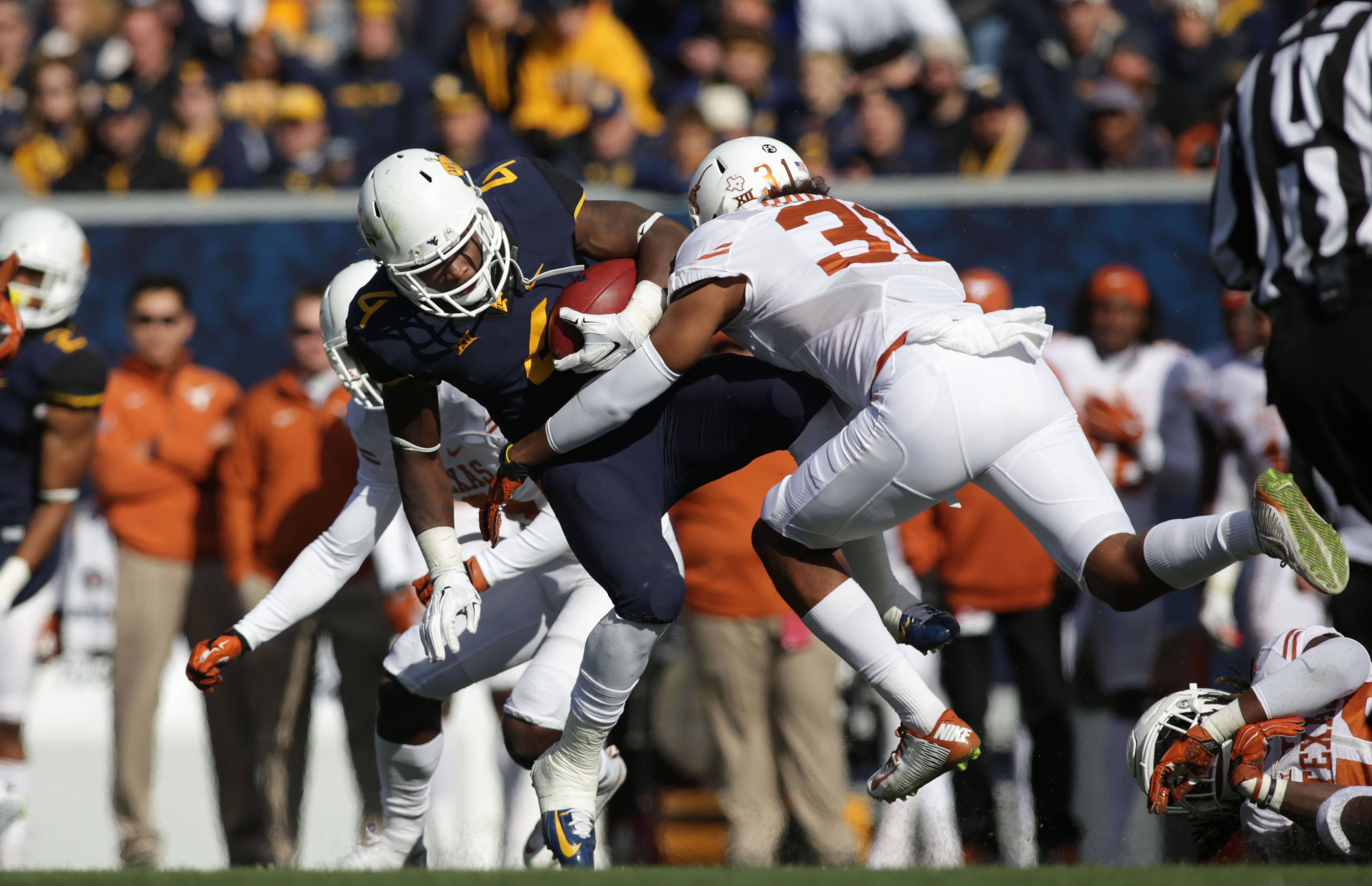 West Virginia running back Wendell Smallwood (4) is tackled by Texas safety Jason Hall (31) during the first half of an NCAA college football game, Saturday, Nov. 14, 2015, in Morgantown, W.Va. (AP Photo/Raymond Thompson)