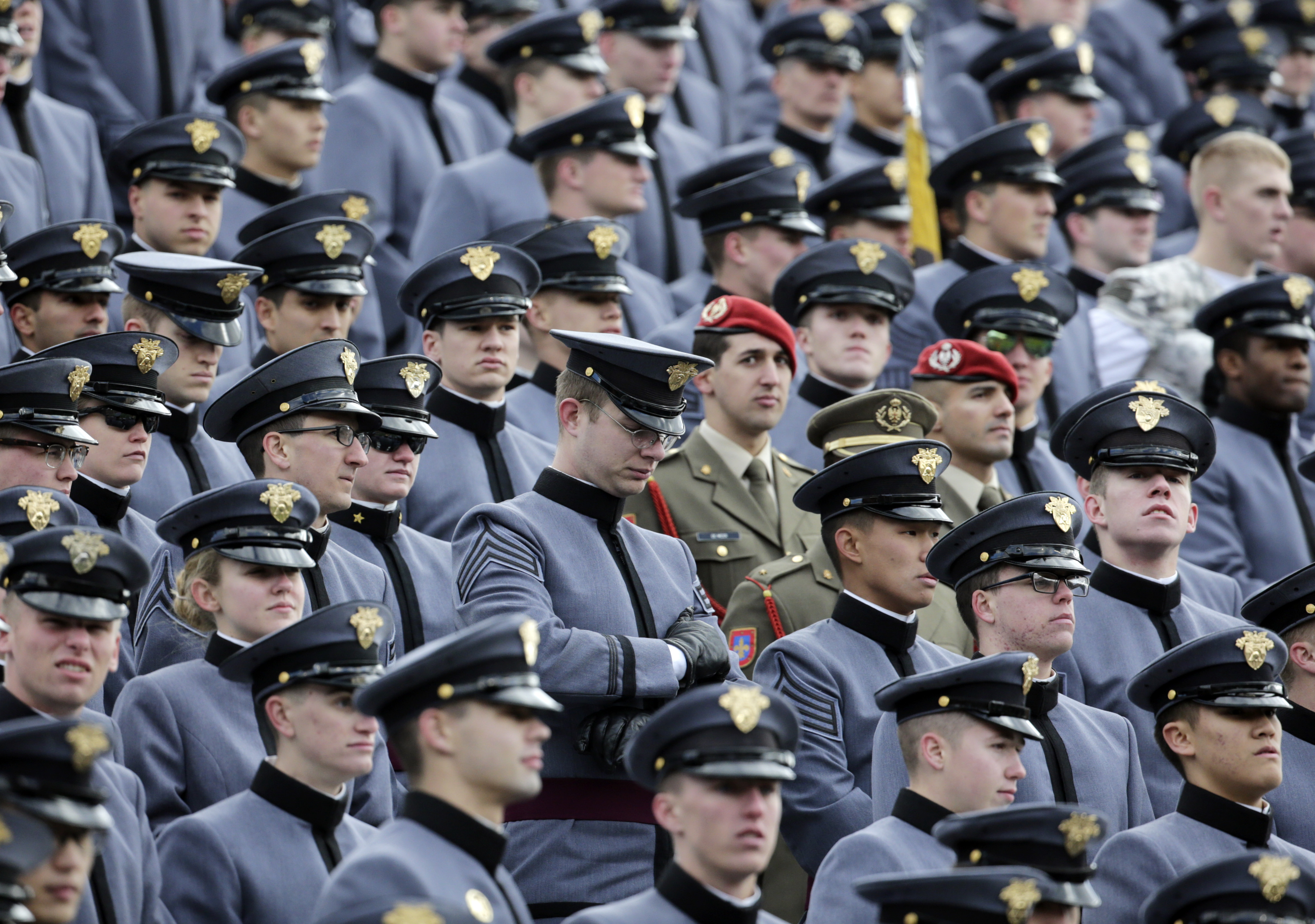 Cadets listen to a public address announcement remembering victims of Friday's attacks in Paris during a timeout in the first half of an NCAA college football game against Tulane on Saturday, Nov. 14, 2015, in West Point, N.Y. (AP Photo/Mike Groll)