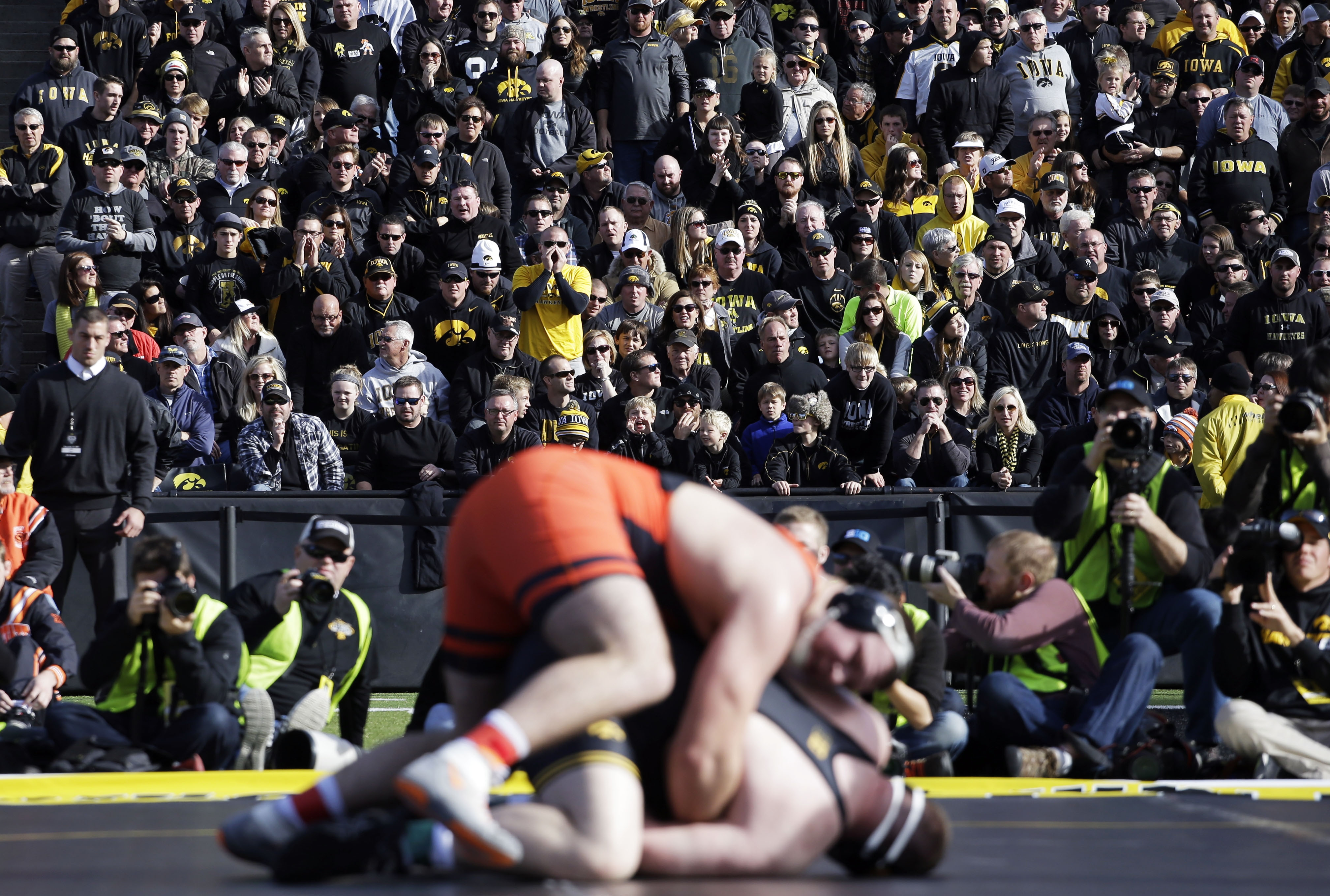 Fans watch Oklahoma State and Iowa grapple during an NCAA wrestling match on the football field at Kinnick Stadium,  Saturday, Nov. 14, 2015, in Iowa City, Iowa. (AP Photo/Nam Y. Huh)