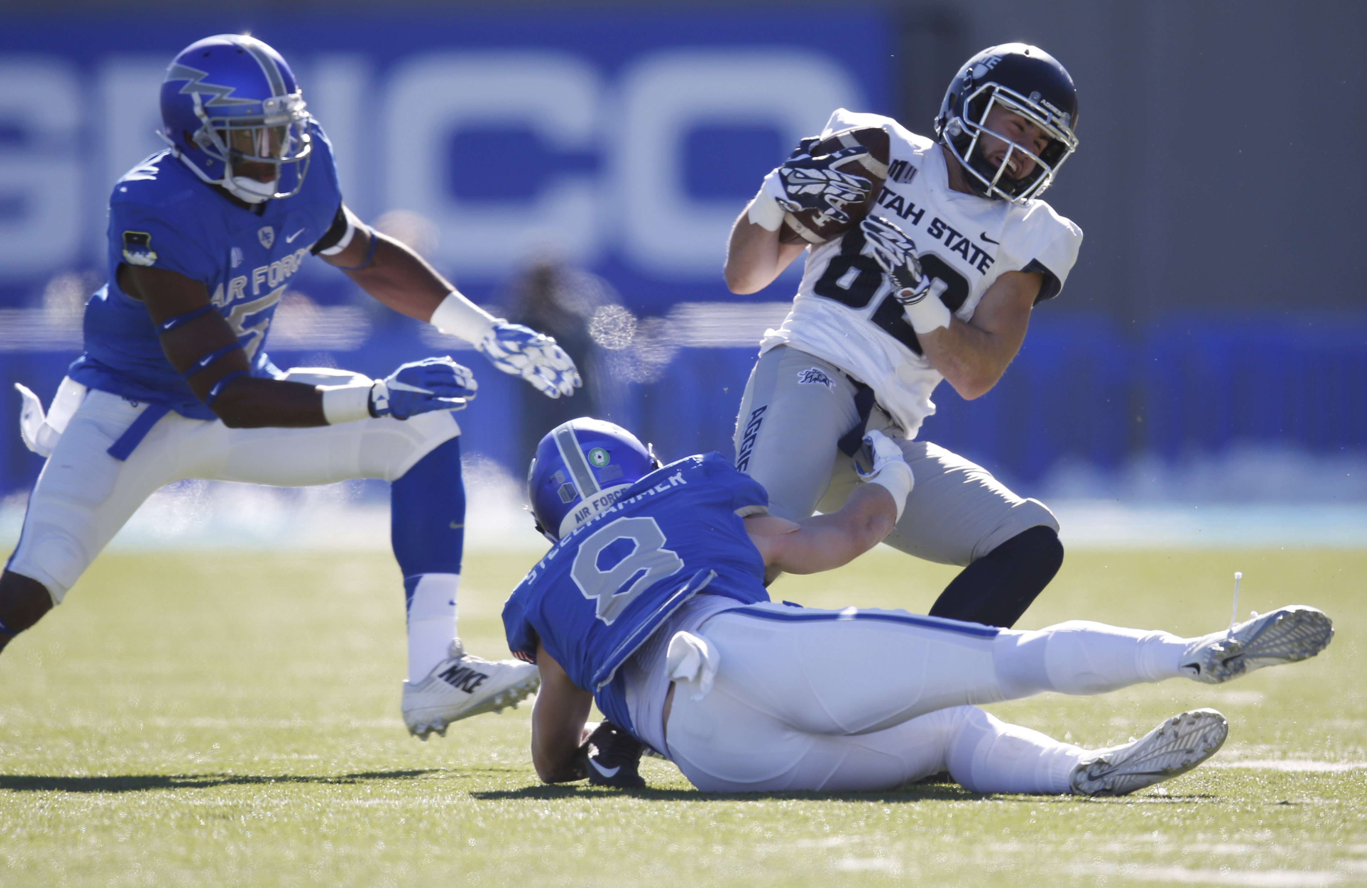 Utah State wide receiver Andrew Rodriguez, back right, is tackled after pulling in a pass by Air Force linebacker Dexter Walker , left, and defensive back Weston Steelhammer in the first half of an NCAA college football game Saturday, Nov. 14, 2015, at Ai