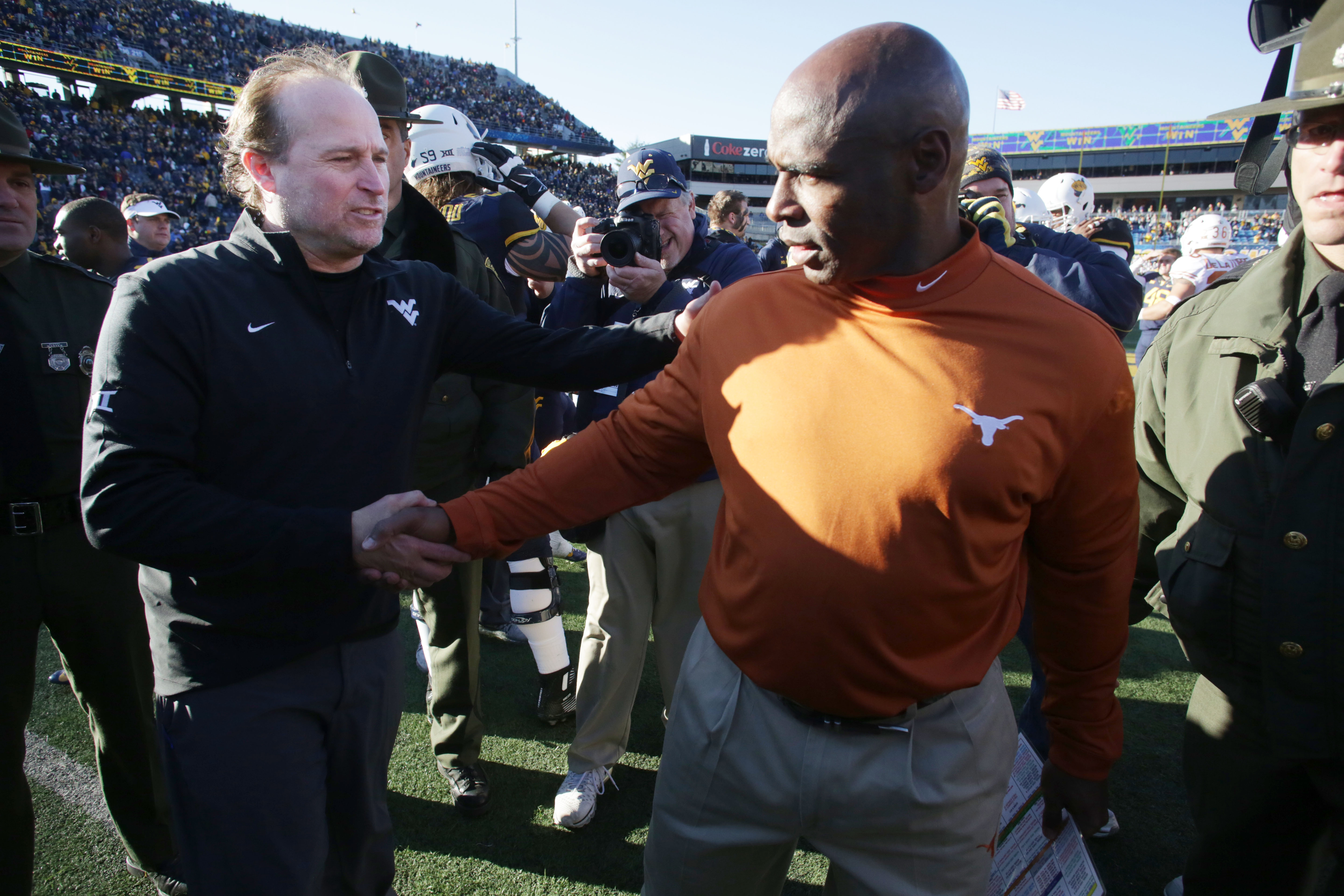 West Virginia head coach Dana Holgorsen, left, and Texas head coach Charlie Strong shakes hands at the end of an NCAA college football game, Saturday, Nov. 14, 2015, in Morgantown, W.Va. (AP Photo/Raymond Thompson)