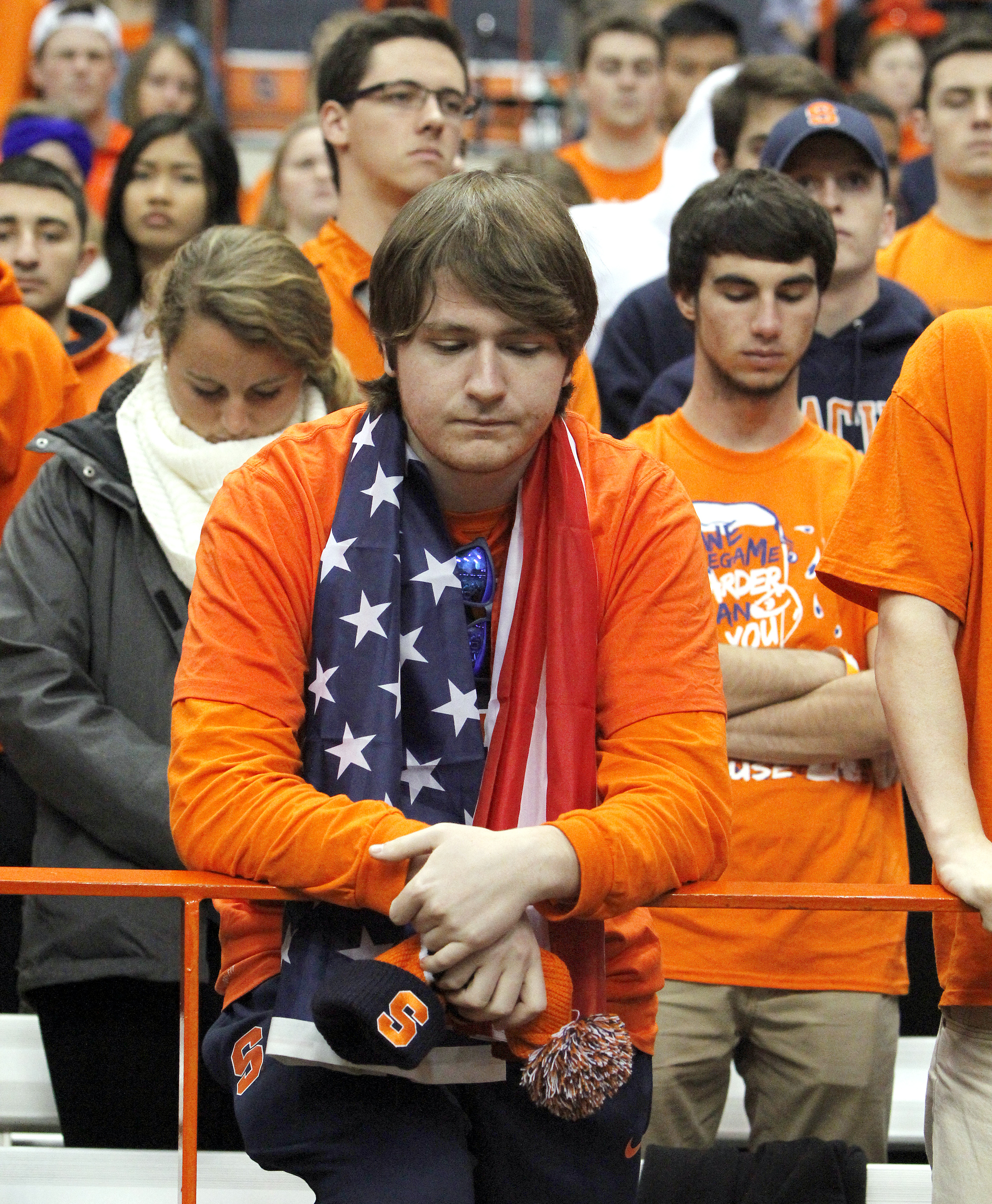 Jake Narracci, of North Branford, Conn., observes a moment of silence for the victims of the attacks in Paris before an NCAA college football game between Clemson and Syracuse in Syracuse, N.Y., Saturday, Nov. 14, 2015. (AP Photo/Nick Lisi)
