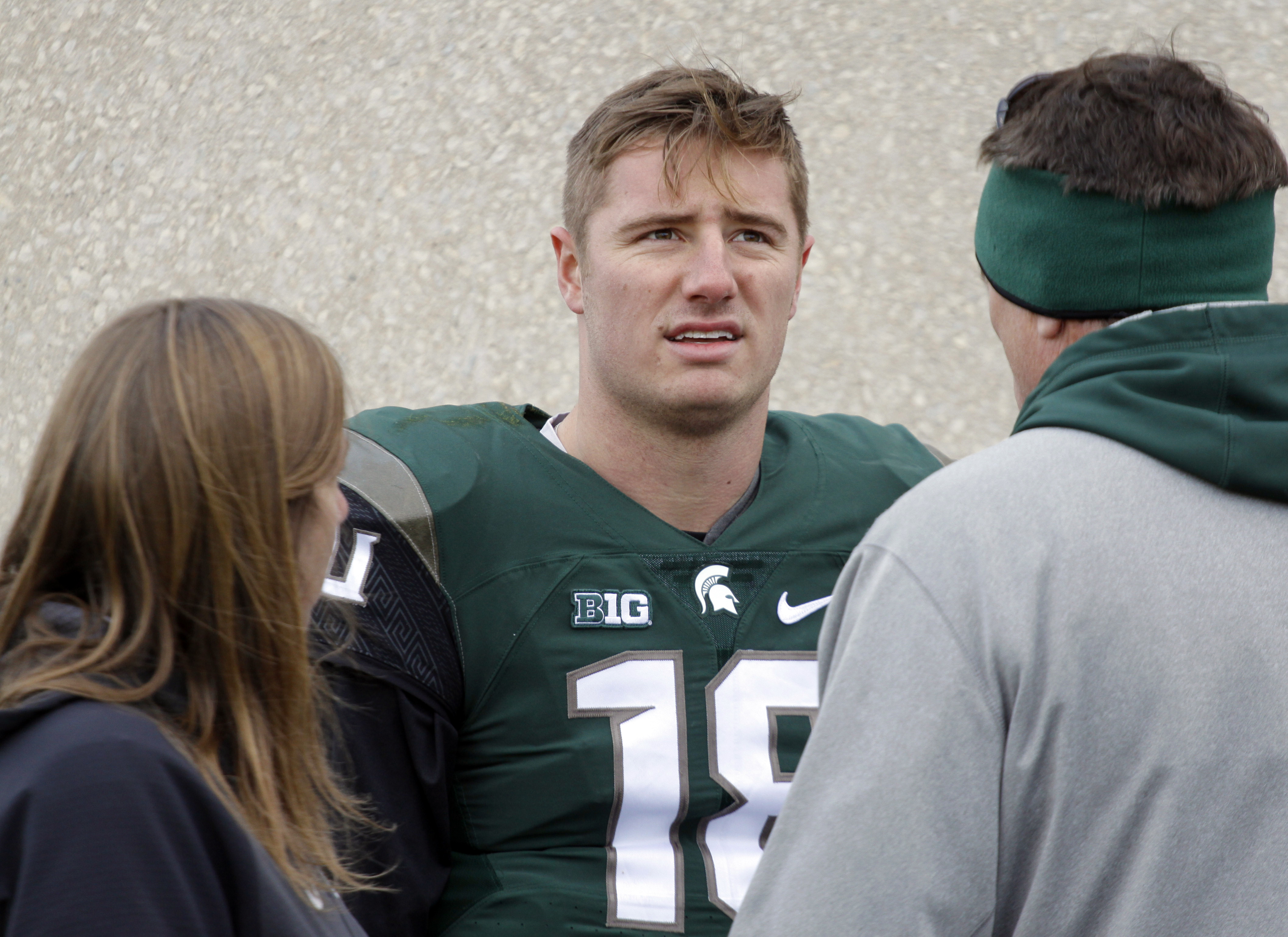 Michigan State quarterback Connor Cook, center, talks with team trainer Sally Nogle, left, and his father, Chris Cook, right, following an NCAA college football game against Maryland, Saturday, Nov. 14, 2015, in East Lansing, Mich. Michigan State won 24-7