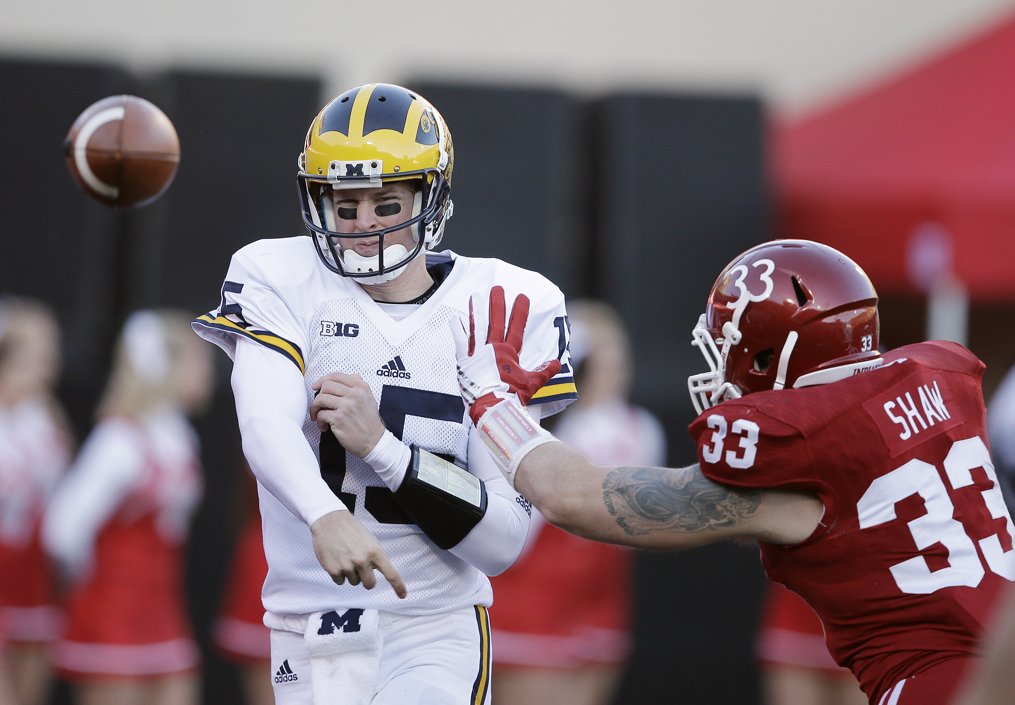 Michigan's Jake Rudock (15) throws while being pressured by Indiana's Zack Shaw (33) during the first half of an NCAA college football game Saturday, Nov. 14, 2015, in Bloomington, Ind. (AP Photo/Darron Cummings)