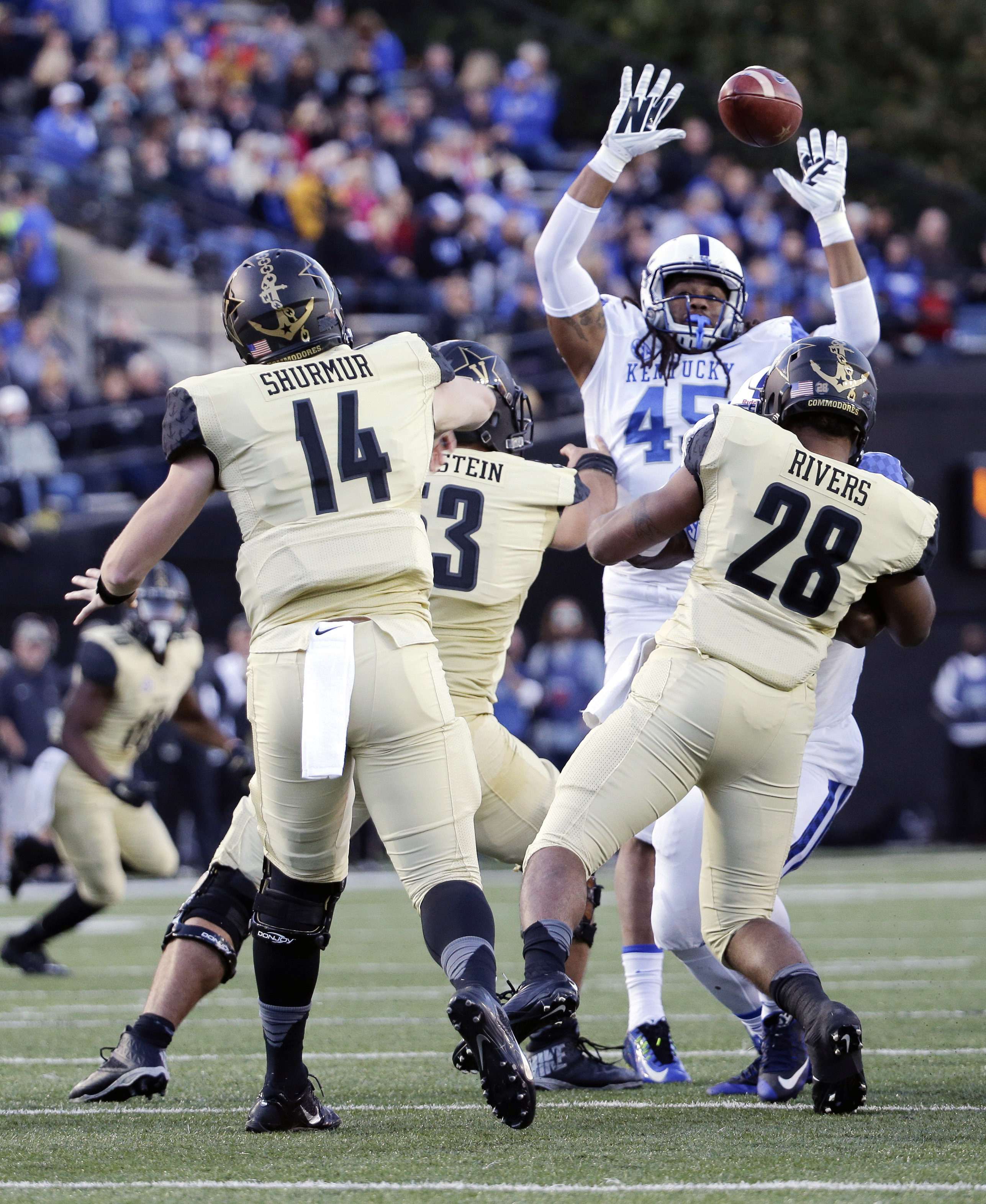 Vanderbilt quarterback Kyle Shurmur (14) passes over the reach of Kentucky linebacker Josh Forrest (45) in the first half of an NCAA college football game Saturday, Nov. 14, 2015, in Nashville, Tenn. (AP Photo/Mark Humphrey)