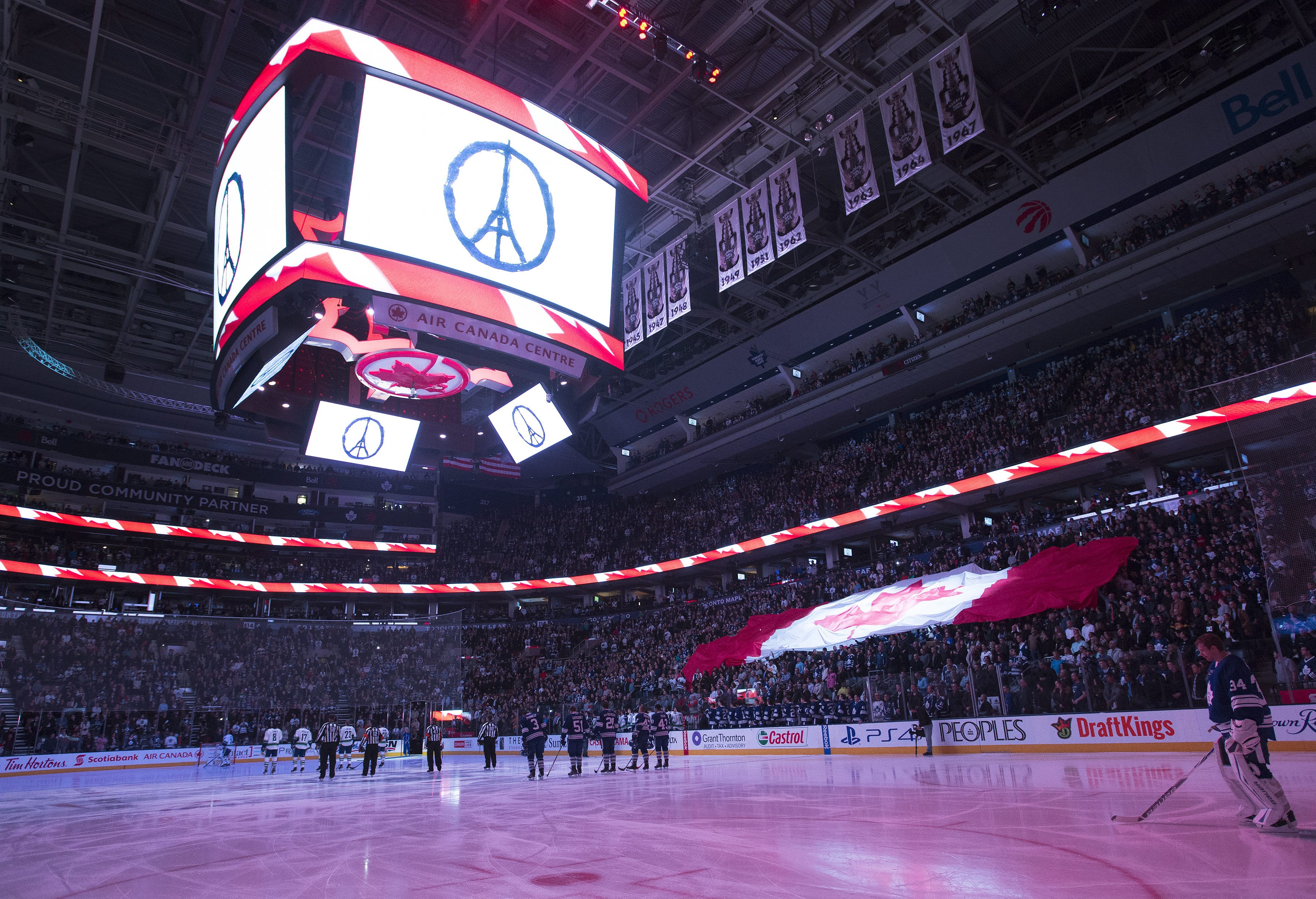 Toronto Maple Leafs and the Vancouver Canucks along with fans sing the Canadian national anthem after taking a moment of silence in support for the France and the City of Paris after recent attacks during first period NHL hockey action in Toronto on Satur